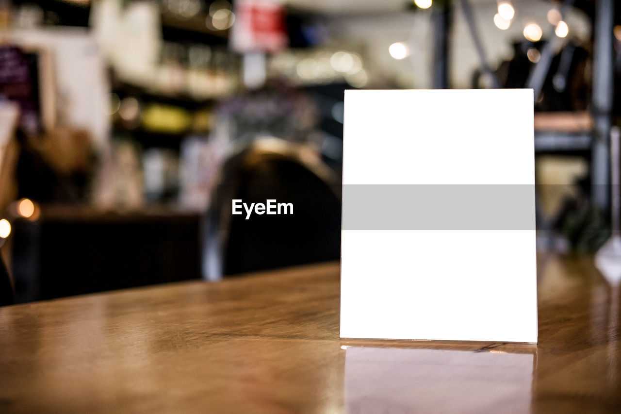 Close-up of empty placard on table in restaurant