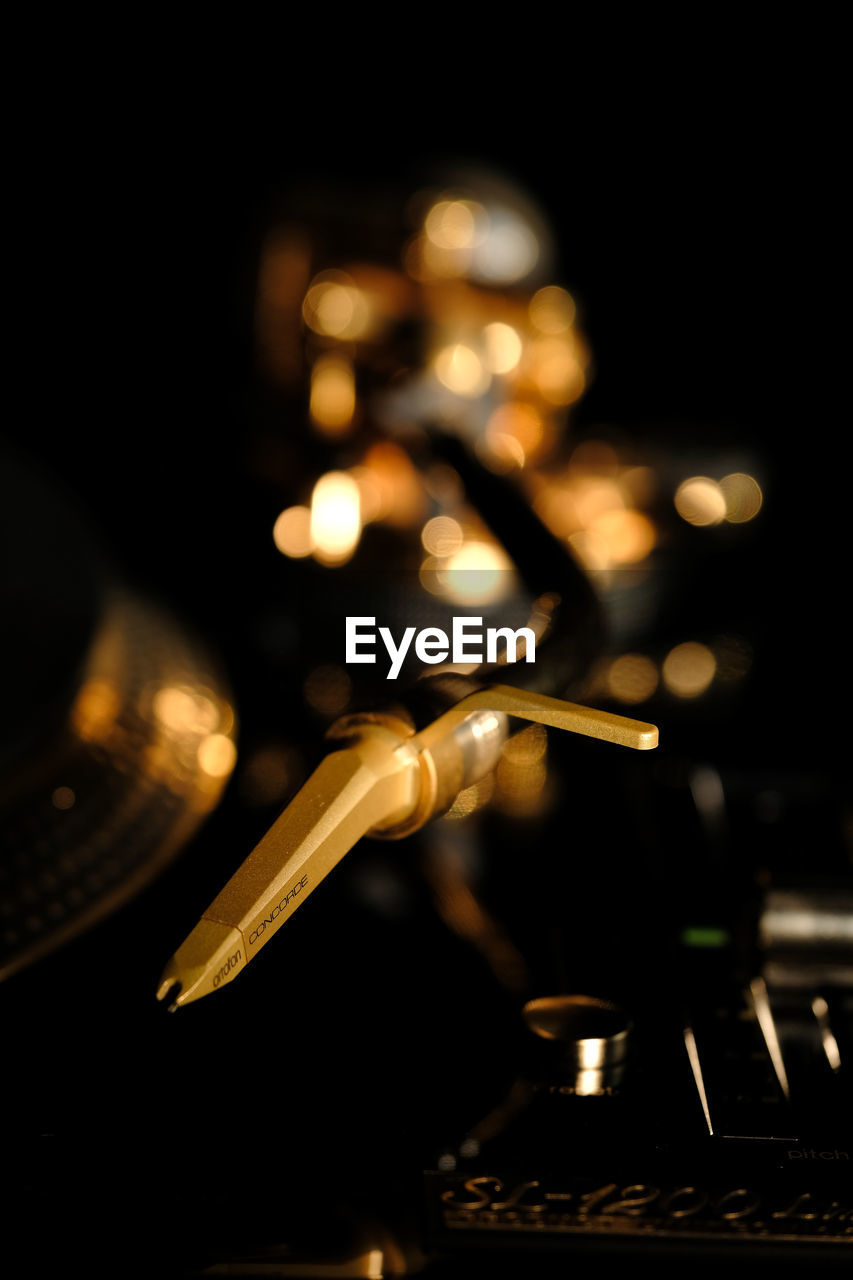 indoors, close-up, no people, selective focus, metal, equipment, illuminated, technology, turntable, record, music, control, audio equipment, focus on foreground, arts culture and entertainment, studio shot, machinery, gold colored, black background