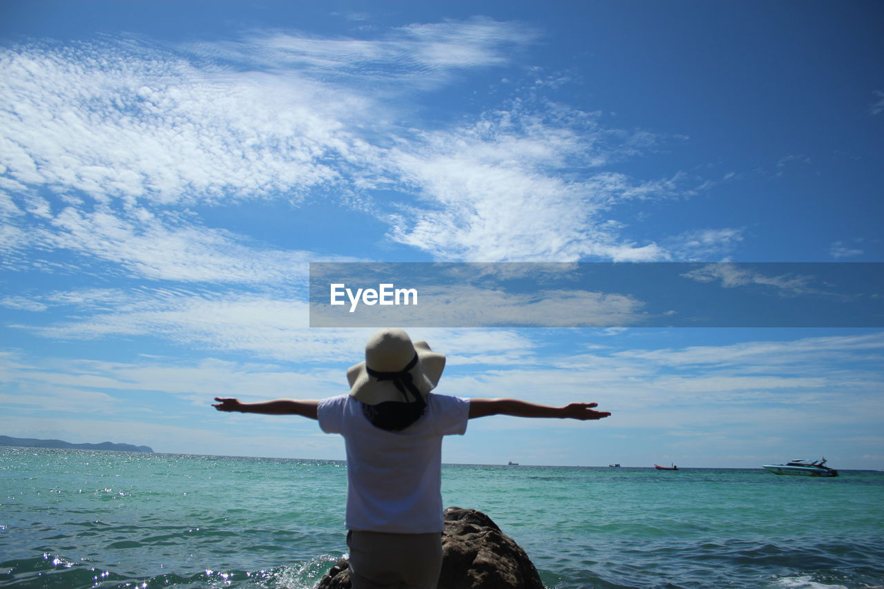 sky, sea, water, one person, rear view, lifestyles, leisure activity, real people, beauty in nature, cloud - sky, scenics - nature, human arm, standing, limb, arms outstretched, horizon over water, nature, vacations, horizon, arms raised, outdoors