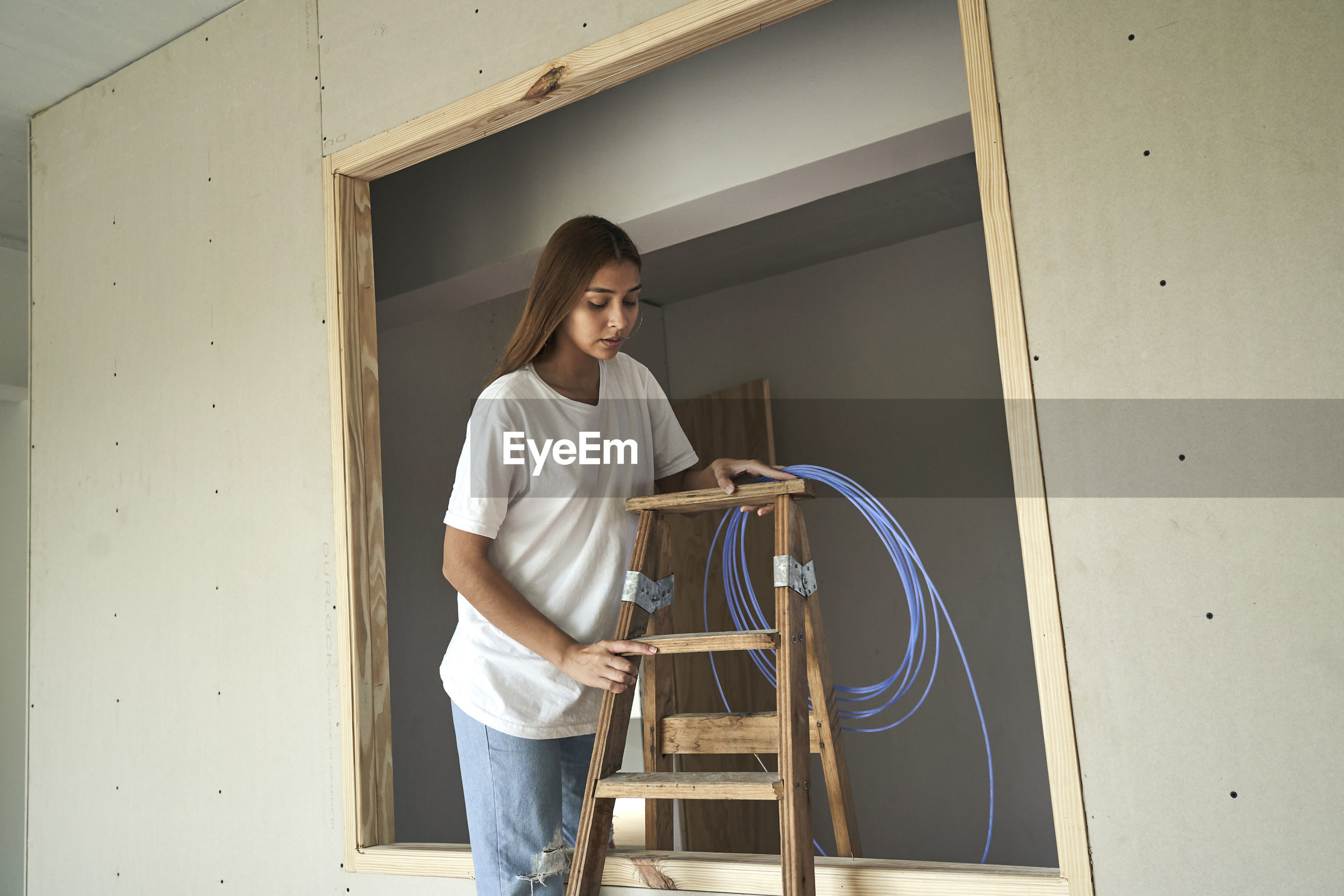 Young female architect working with wooden ladder