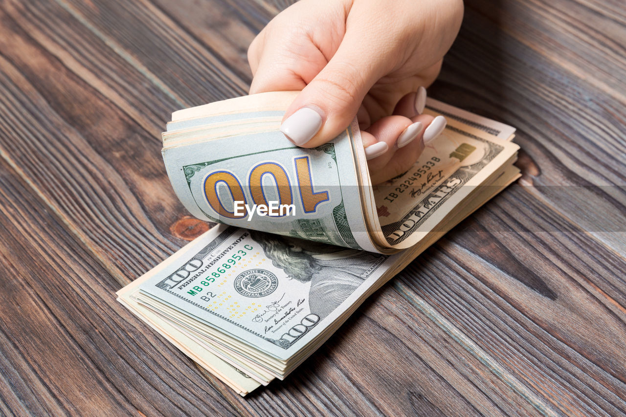 human hand, hand, human body part, one person, finance, paper currency, currency, business, holding, wealth, human finger, wood - material, finger, unrecognizable person, body part, real people, close-up, table, savings
