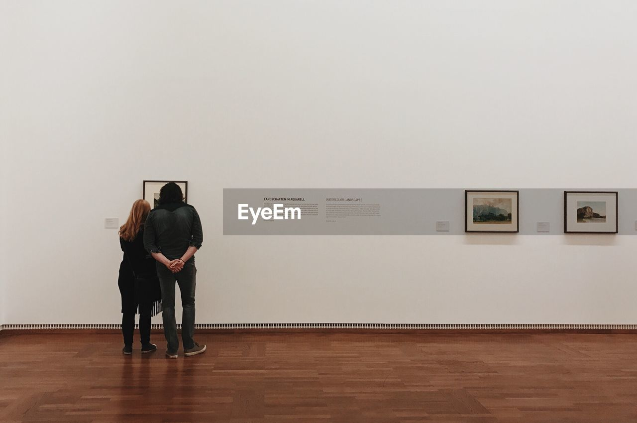 picture frame, hardwood floor, indoors, rear view, standing, men, real people, day, people