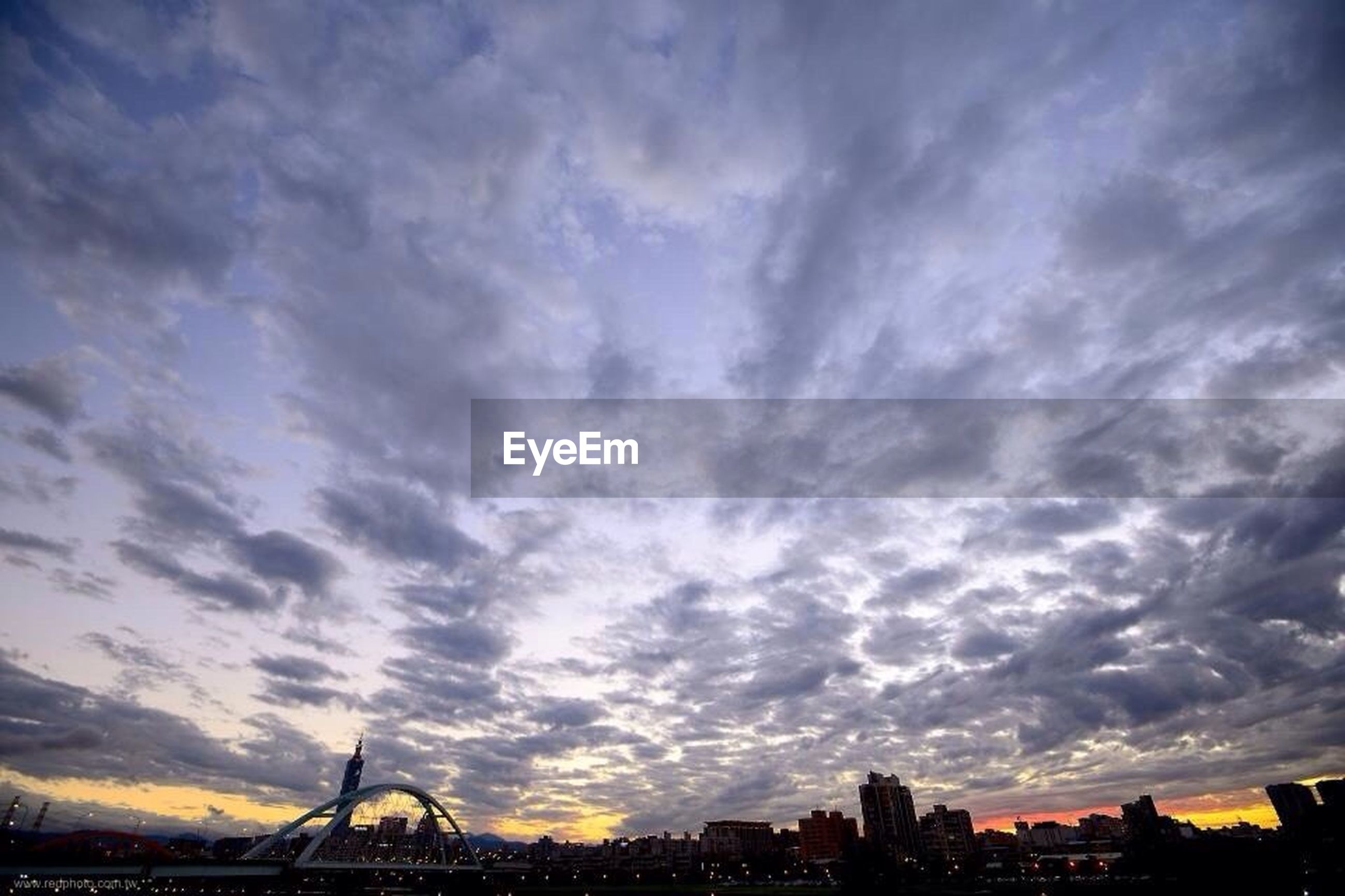Low angle view of cloudy sky above city