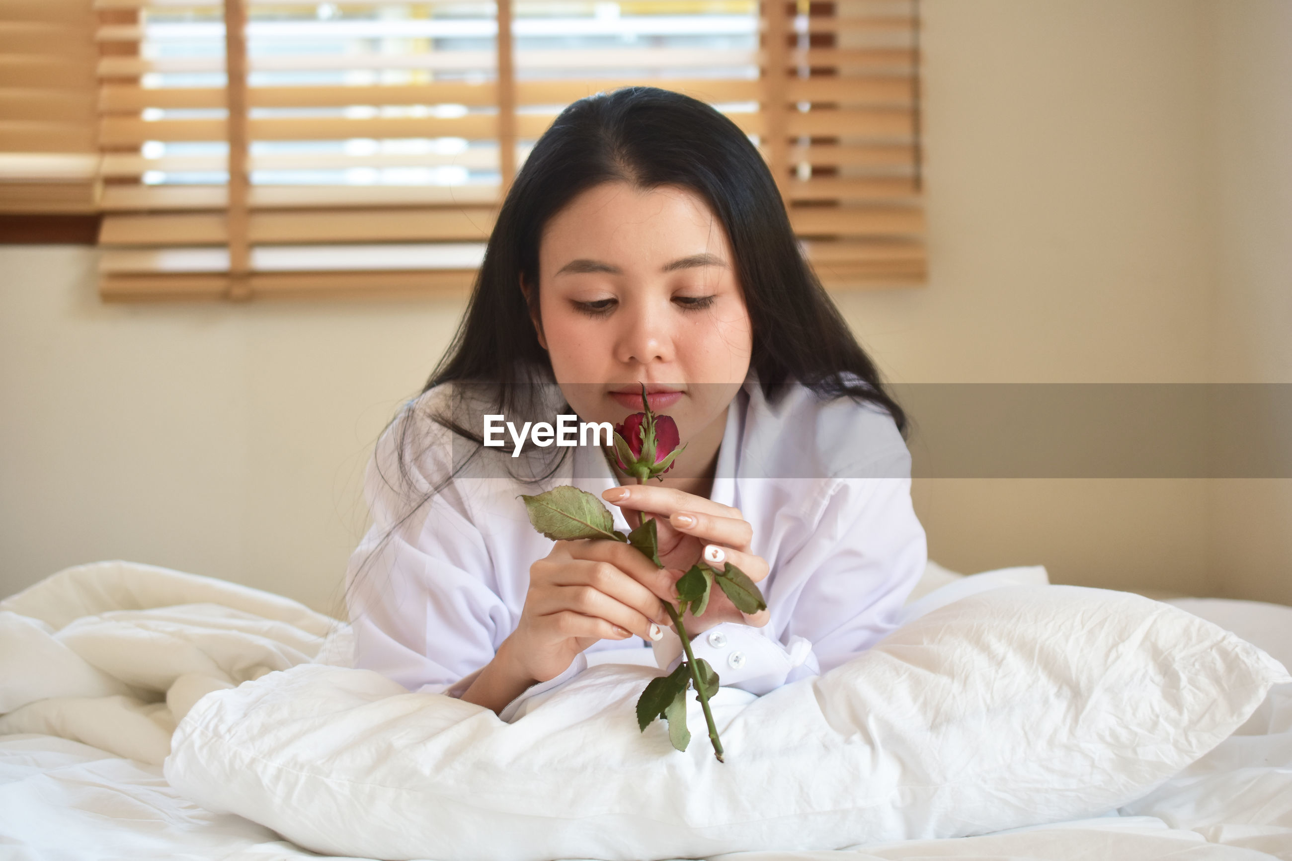 Young woman holding rose while relaxing on bed at home