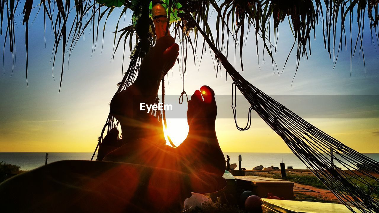 sky, sunset, human hand, real people, hand, sunlight, sun, nature, human body part, one person, lens flare, silhouette, tree, sunbeam, water, plant, unrecognizable person, leisure activity, beauty in nature, lifestyles, outdoors, finger