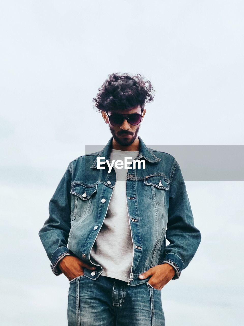 casual clothing, one person, standing, front view, young men, real people, sky, young adult, three quarter length, leisure activity, lifestyles, denim, jeans, fashion, glasses, nature, day, textile, outdoors, hairstyle