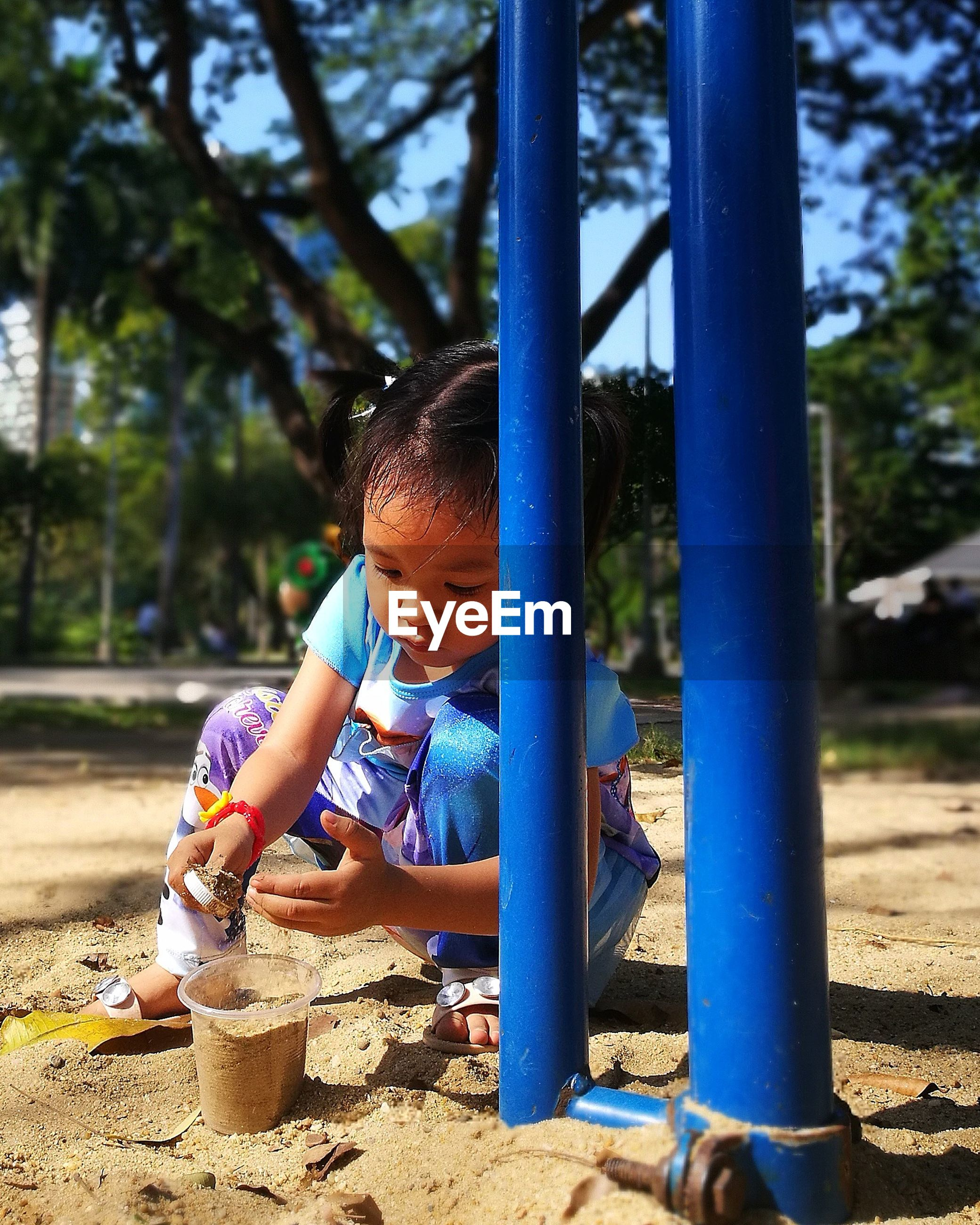Cute girl playing with sand at park