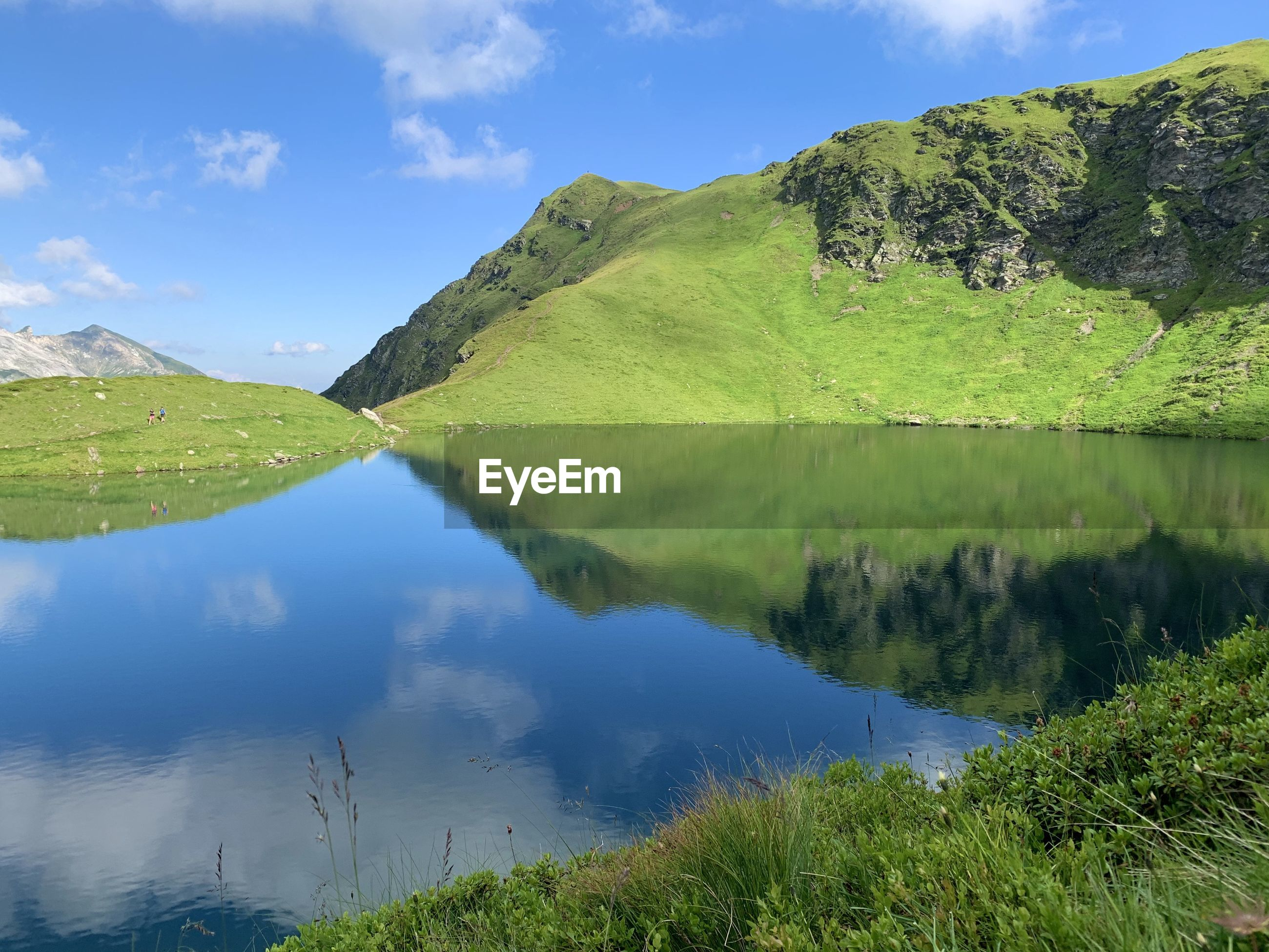 SCENIC VIEW OF LAKE AND GREEN MOUNTAINS AGAINST SKY