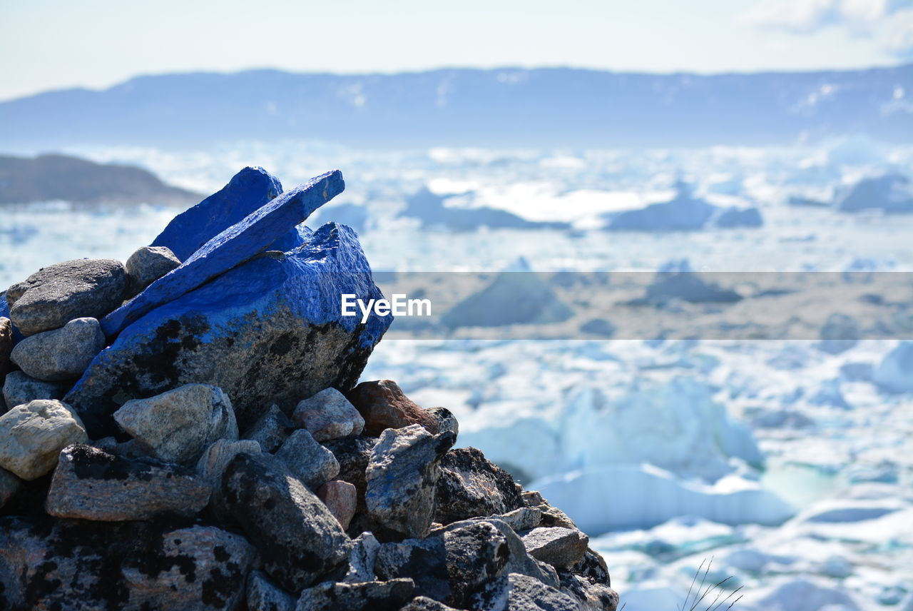 Close-Up Of Blue Painted Rocks During Winter