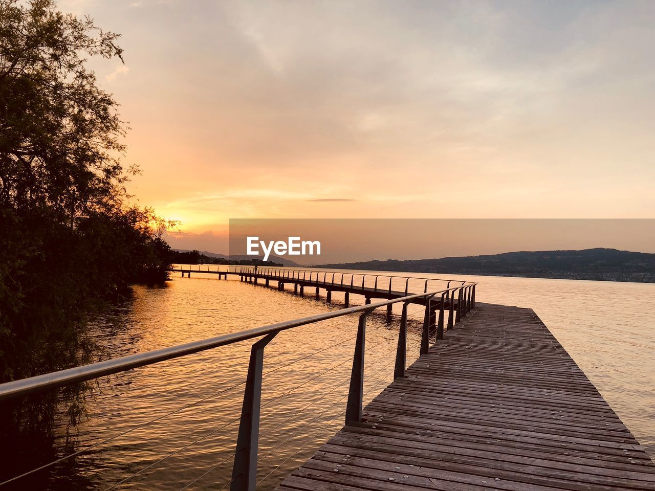 water, sky, sunset, scenics - nature, beauty in nature, tranquility, tranquil scene, nature, railing, cloud - sky, pier, no people, orange color, sea, tree, idyllic, outdoors, jetty, non-urban scene