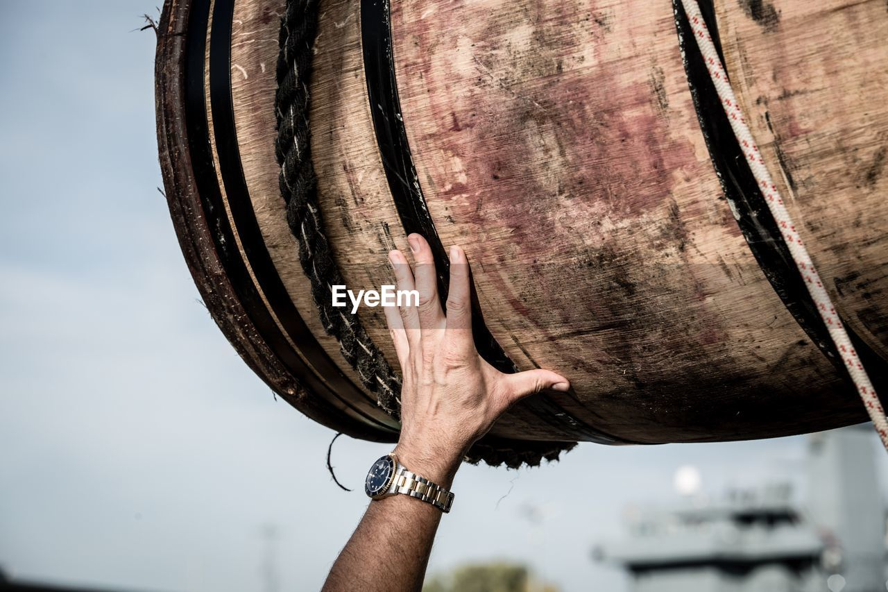 Close-Up Of Hand Touching Wooden Barrel Against Sky