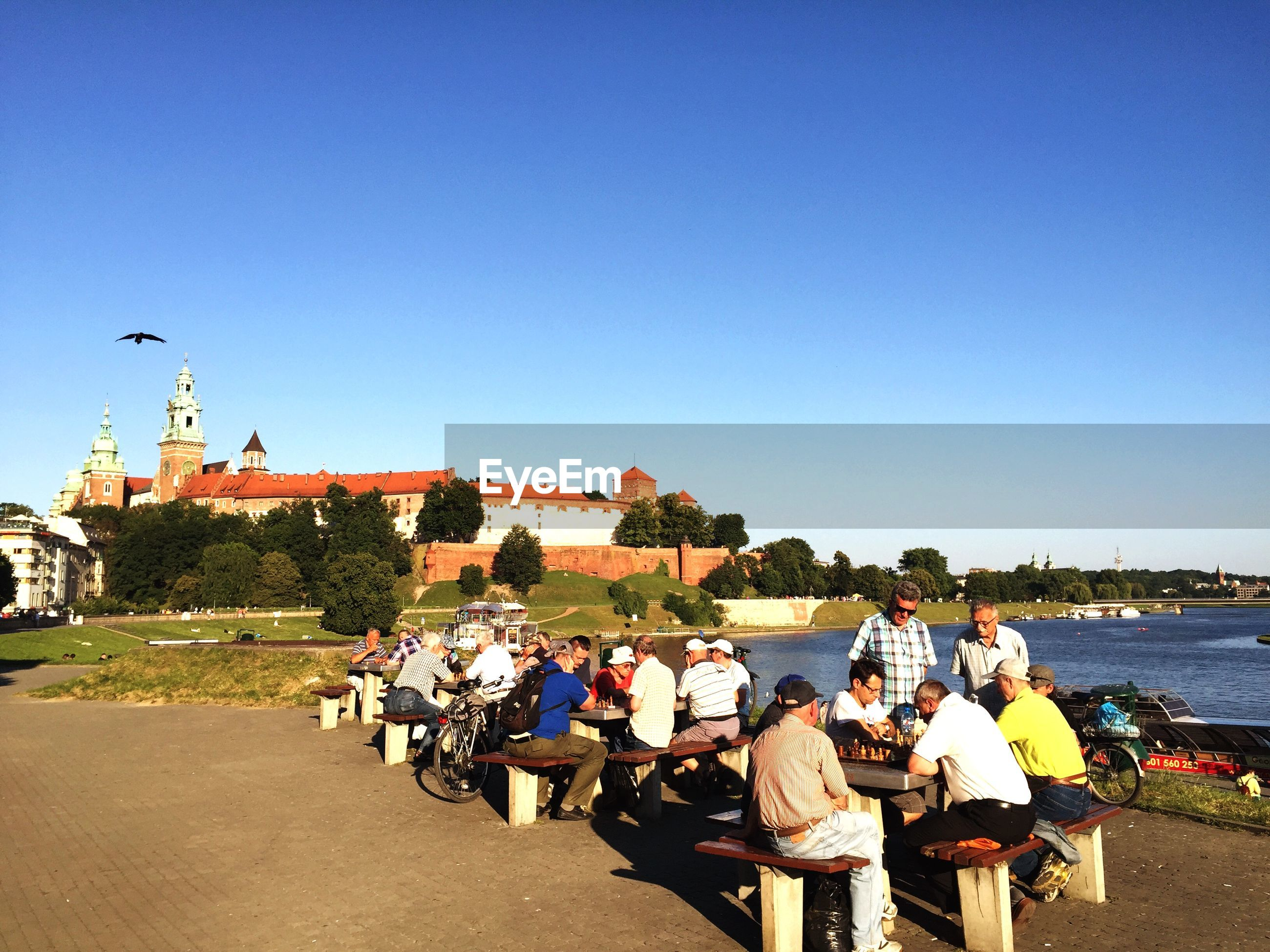 People by tables against clear blue sky