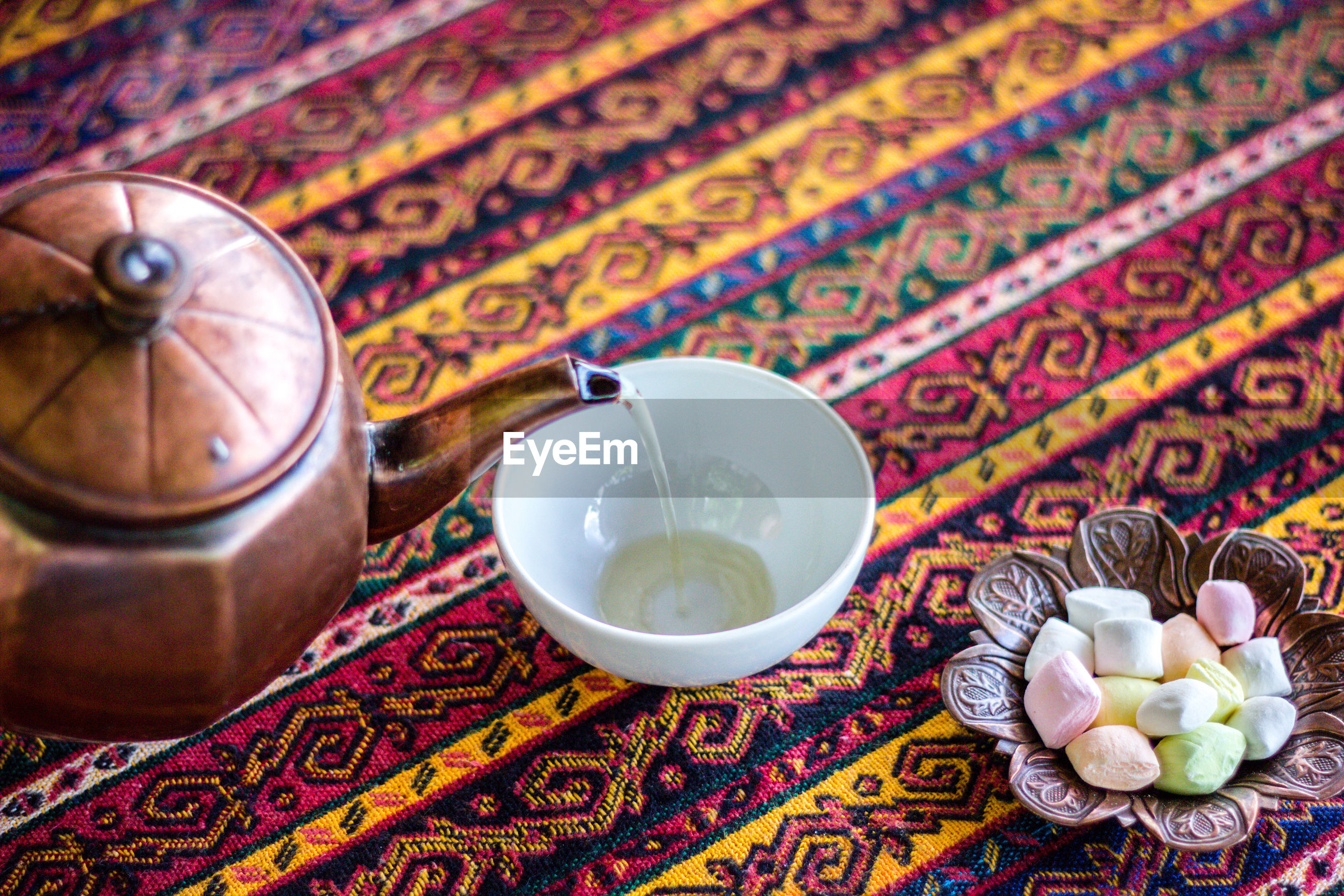 Close-up of tea pouring in cup on table