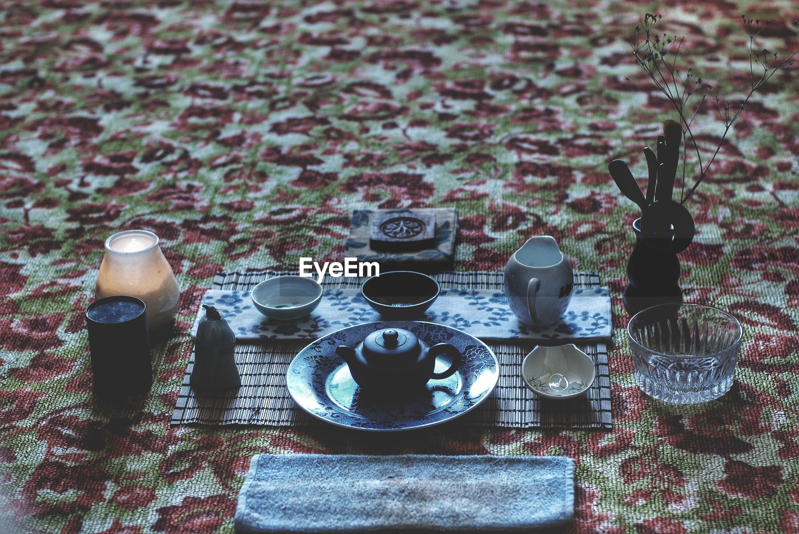 High angle view of crockery arranged on carpet during tea ceremony