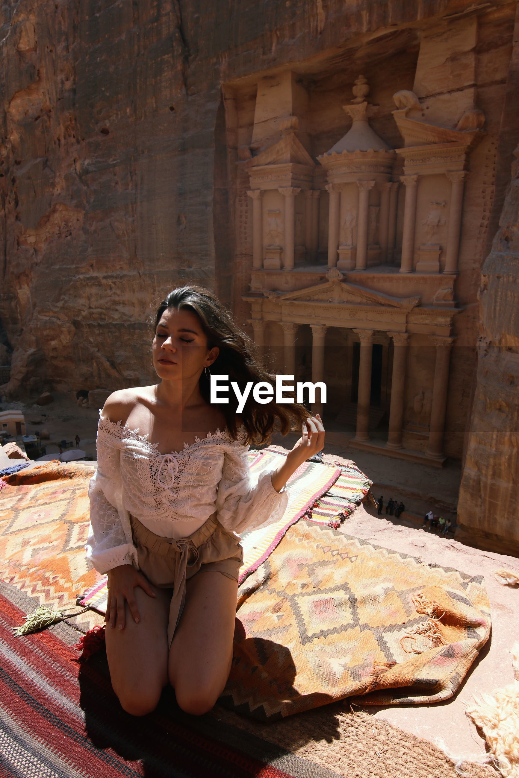 Young woman looking down while sitting outdoors un front of petra treasure building