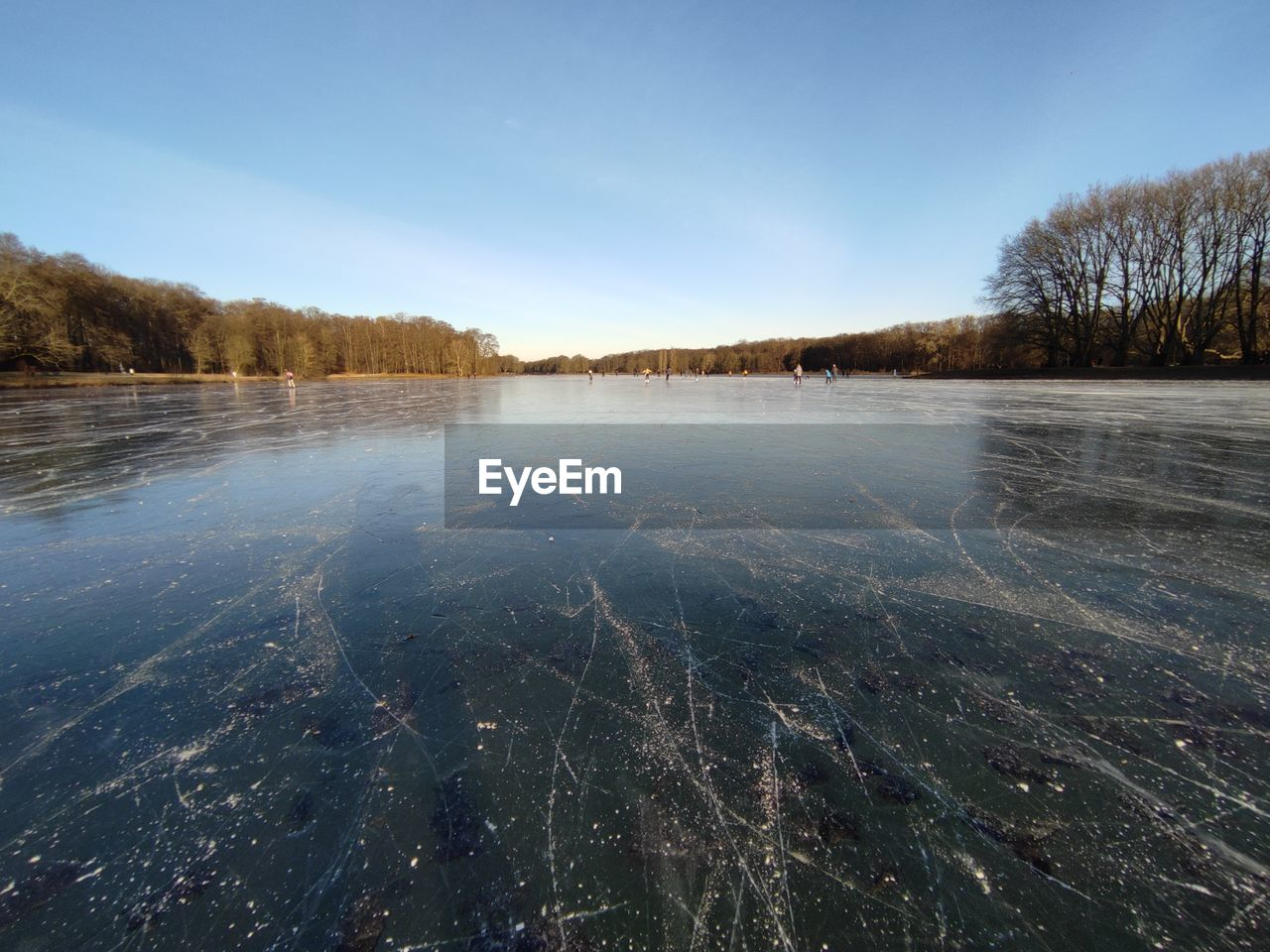 VIEW OF FROZEN LAKE AGAINST SKY