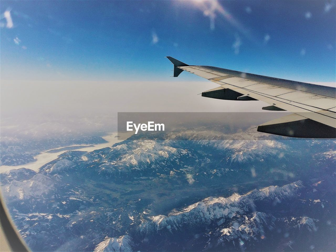 AERIAL VIEW OF AIRCRAFT WING OVER SNOWCAPPED LANDSCAPE AGAINST SKY