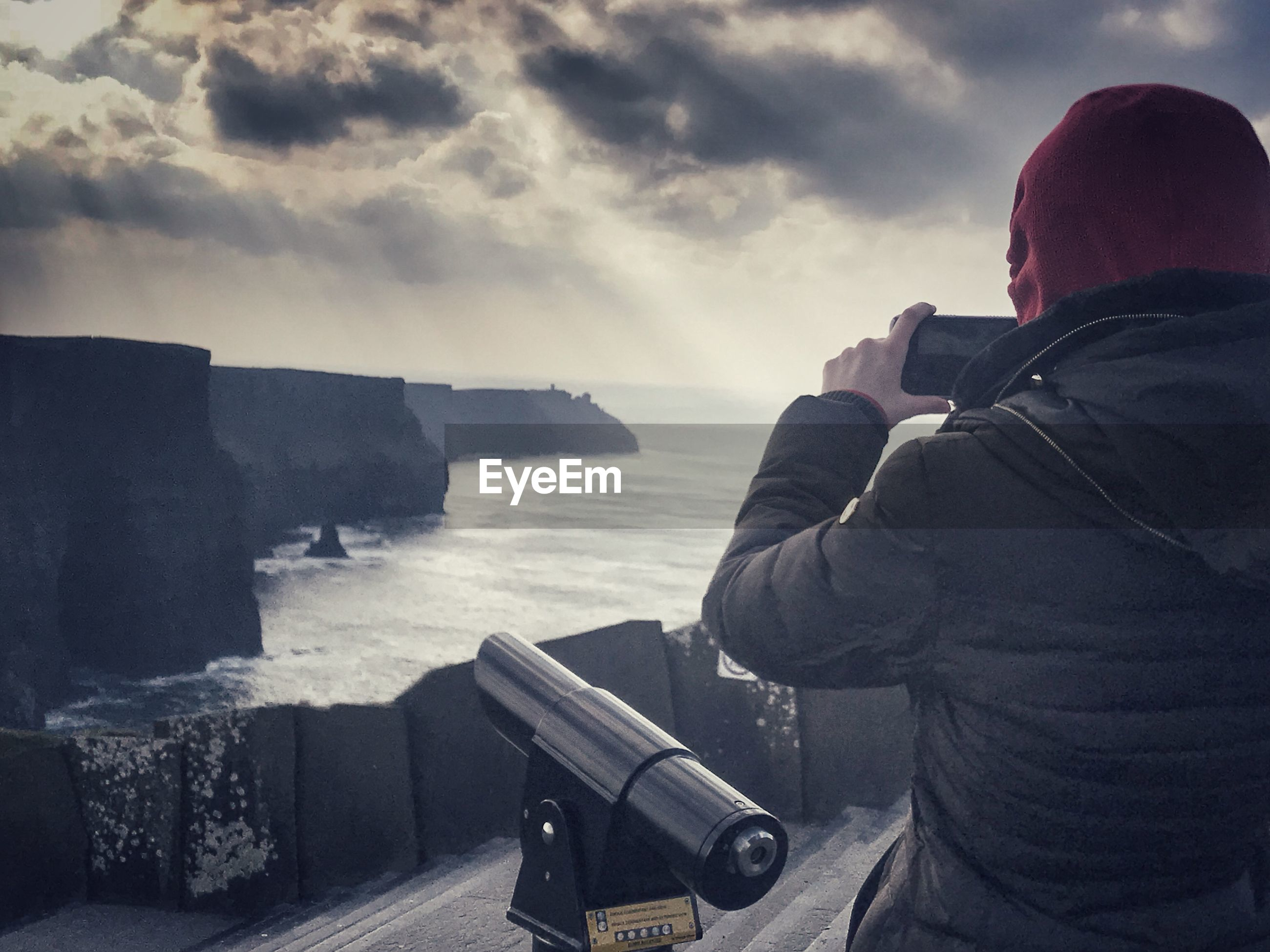Rear view of person photographing sea against cloudy sky