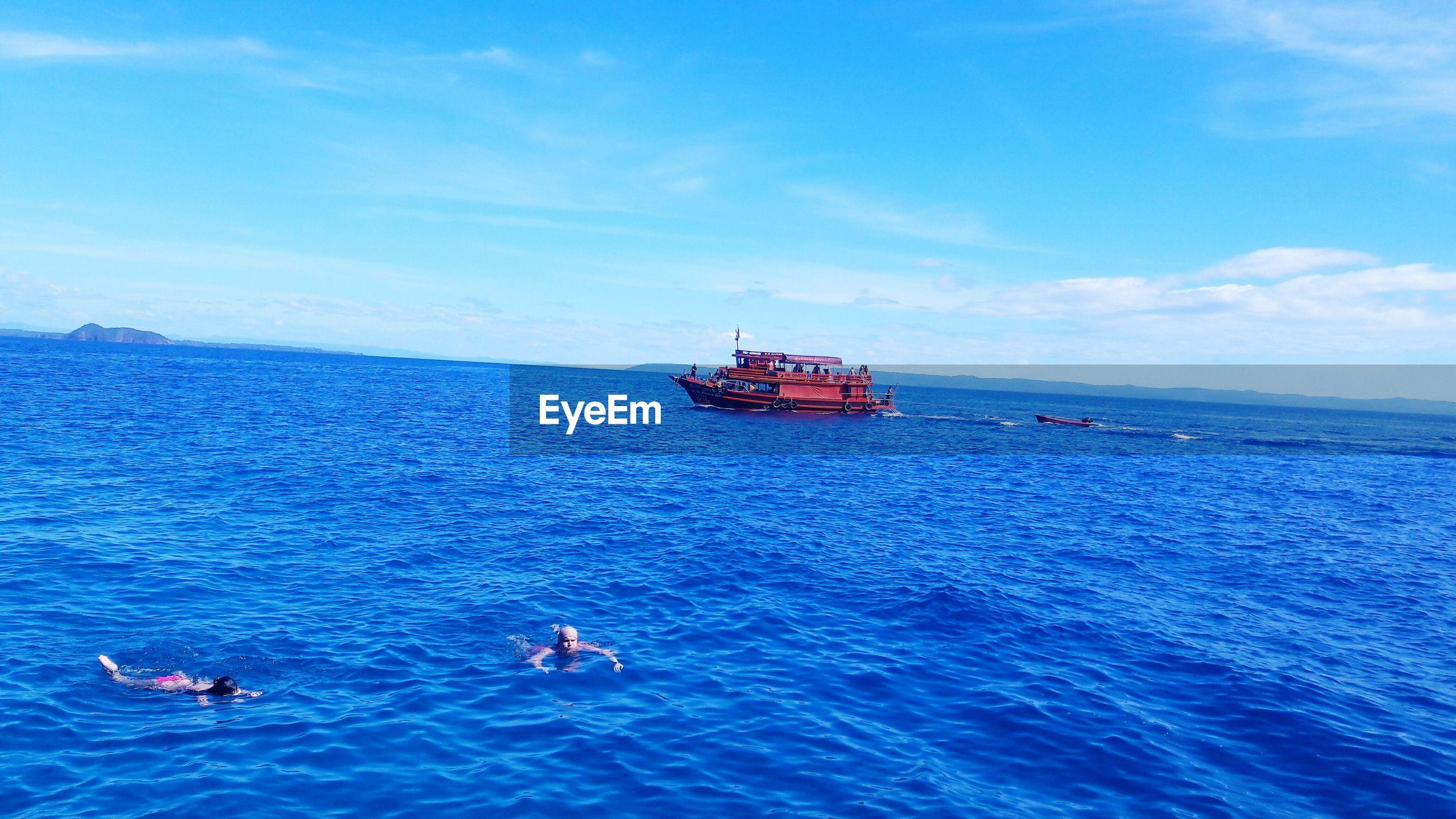 Friends swimming in sea against blue sky