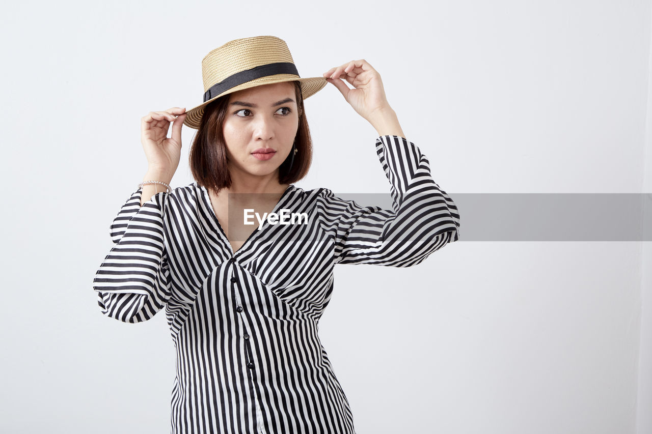 Woman looking away wearing hat standing against white background