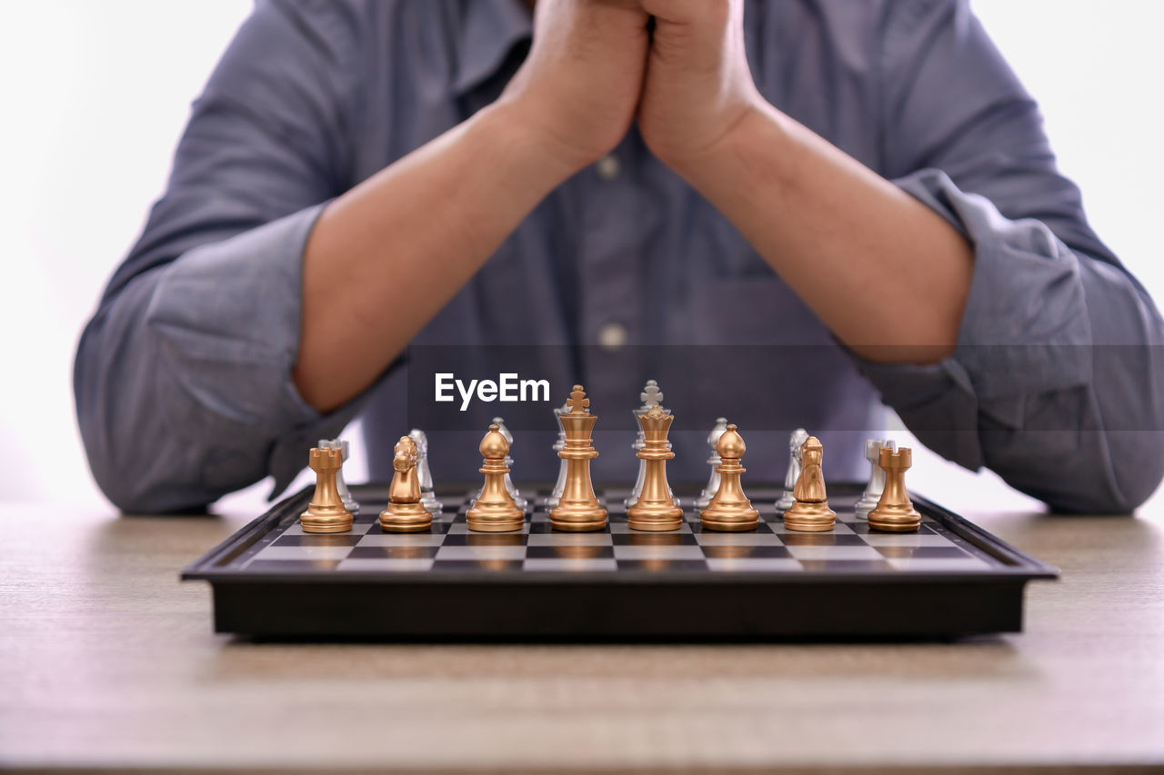Mid section of man playing on chess against white background