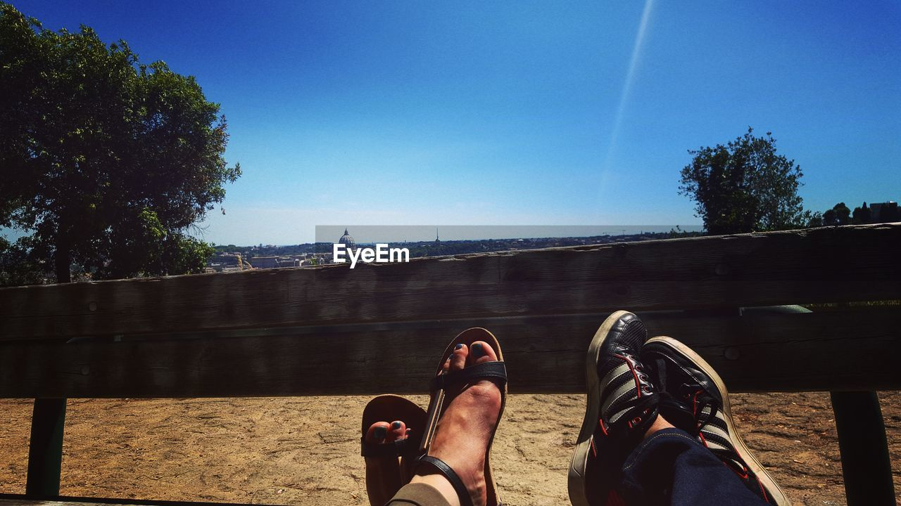 human body part, body part, human leg, personal perspective, low section, nature, sky, shoe, tree, day, real people, people, clear sky, blue, human foot, sunlight, plant, architecture, relaxation, outdoors, vapor trail
