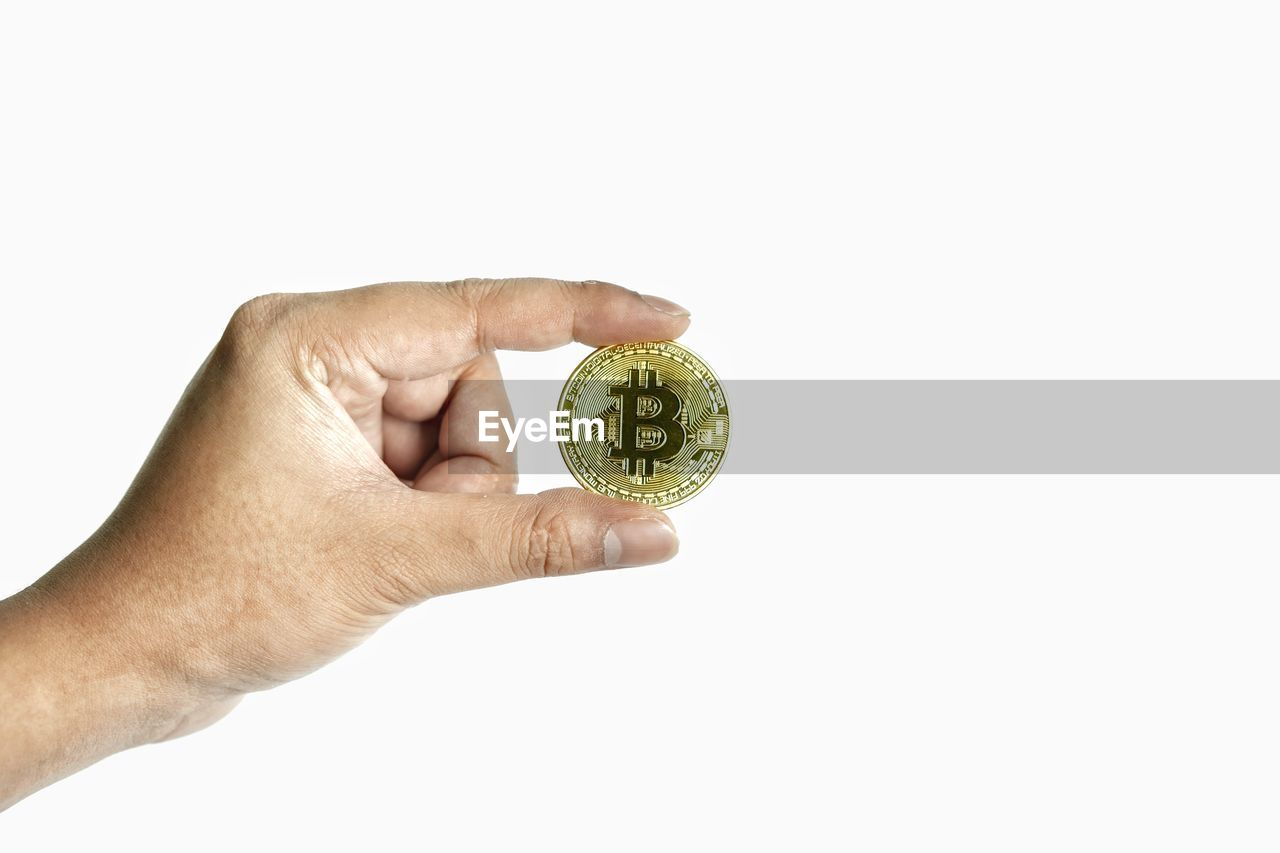 CLOSE-UP OF PERSON HAND HOLDING RING AGAINST WHITE BACKGROUND