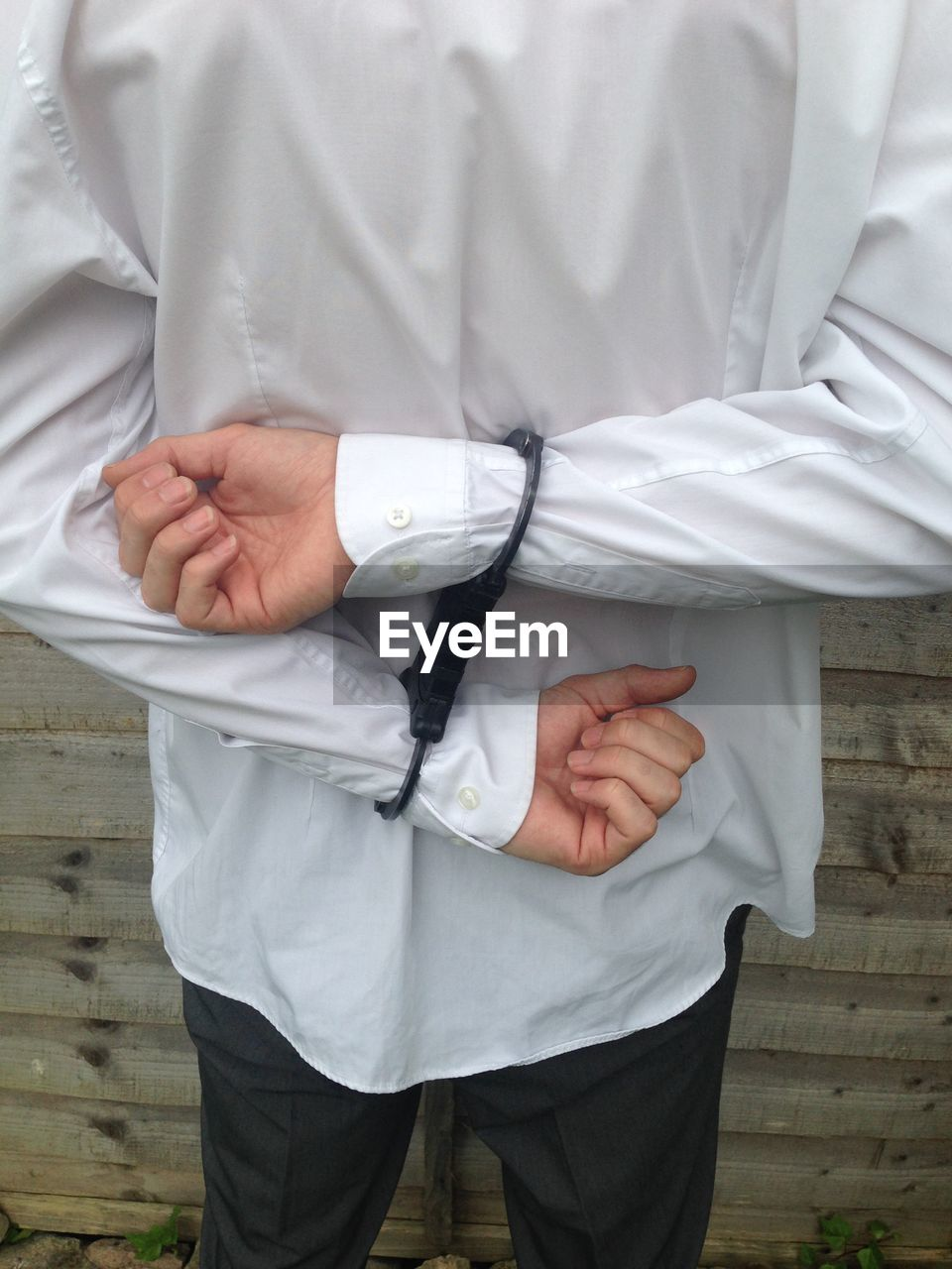 Midsection of man wearing handcuffs