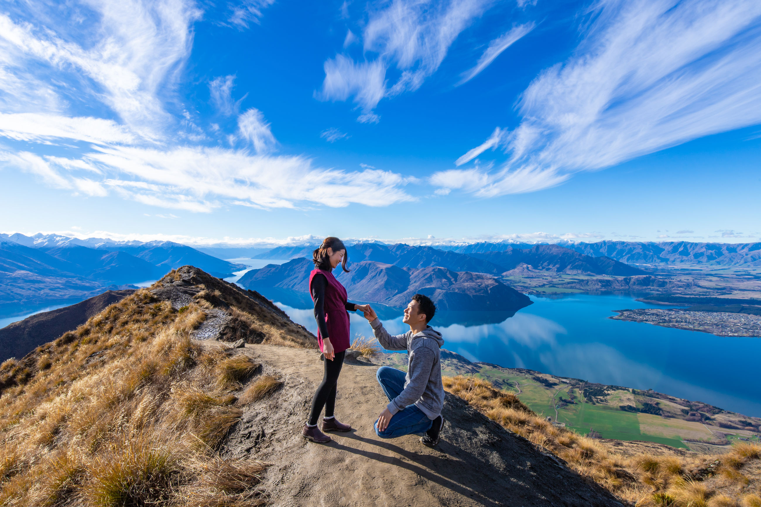 High angle view of boyfriend proposing girlfriend on hill against sky