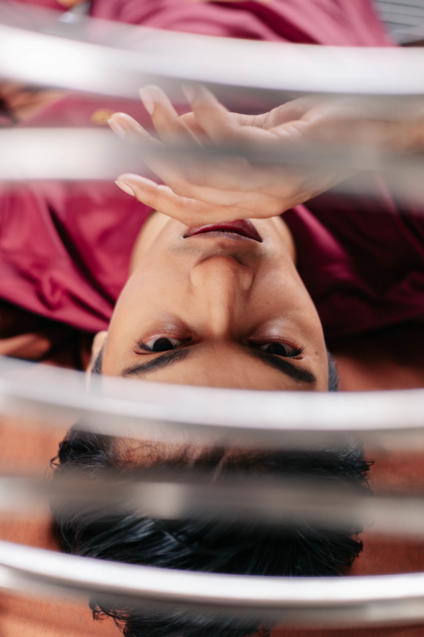portrait, young adult, real people, headshot, one person, front view, indoors, lifestyles, adult, young women, lying down, leisure activity, women, looking at camera, human body part, selective focus, body part, relaxation, human face, teenager