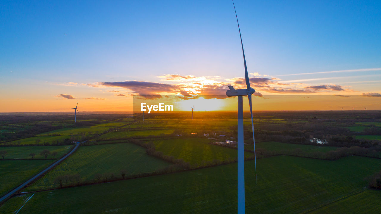 Aerial view of windmills on landscape against sky during sunset