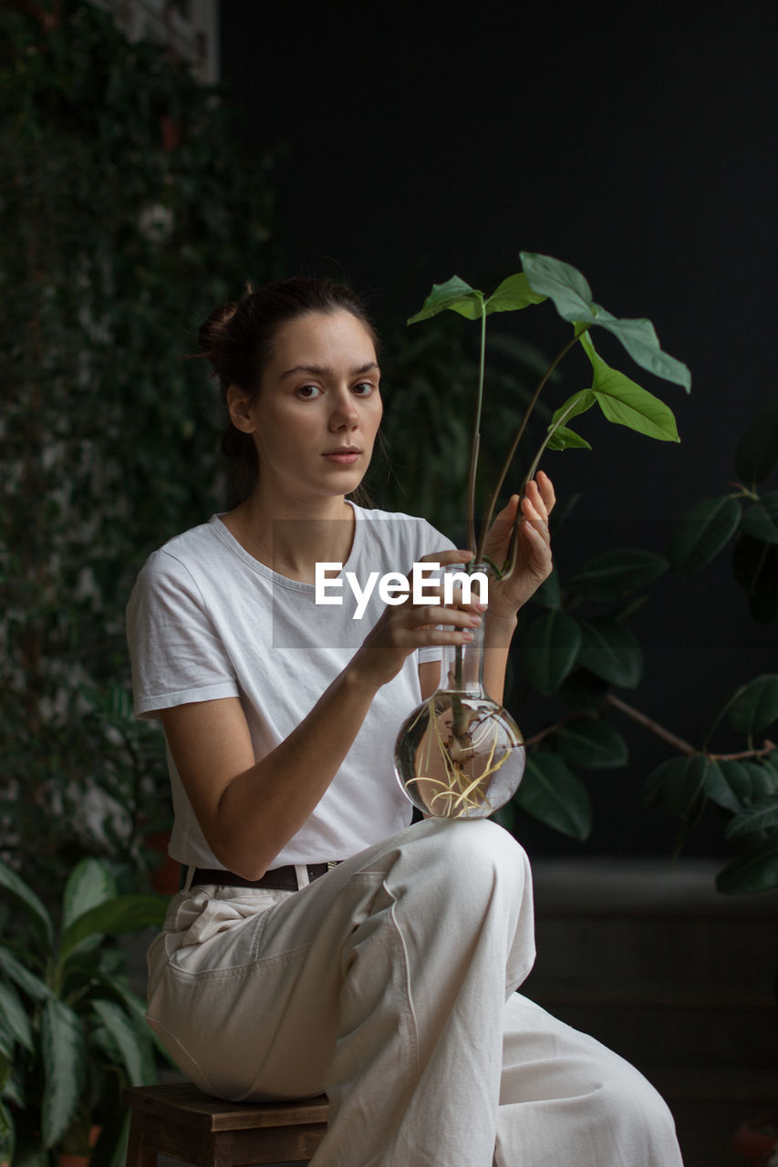 YOUNG WOMAN SITTING BY PLANT