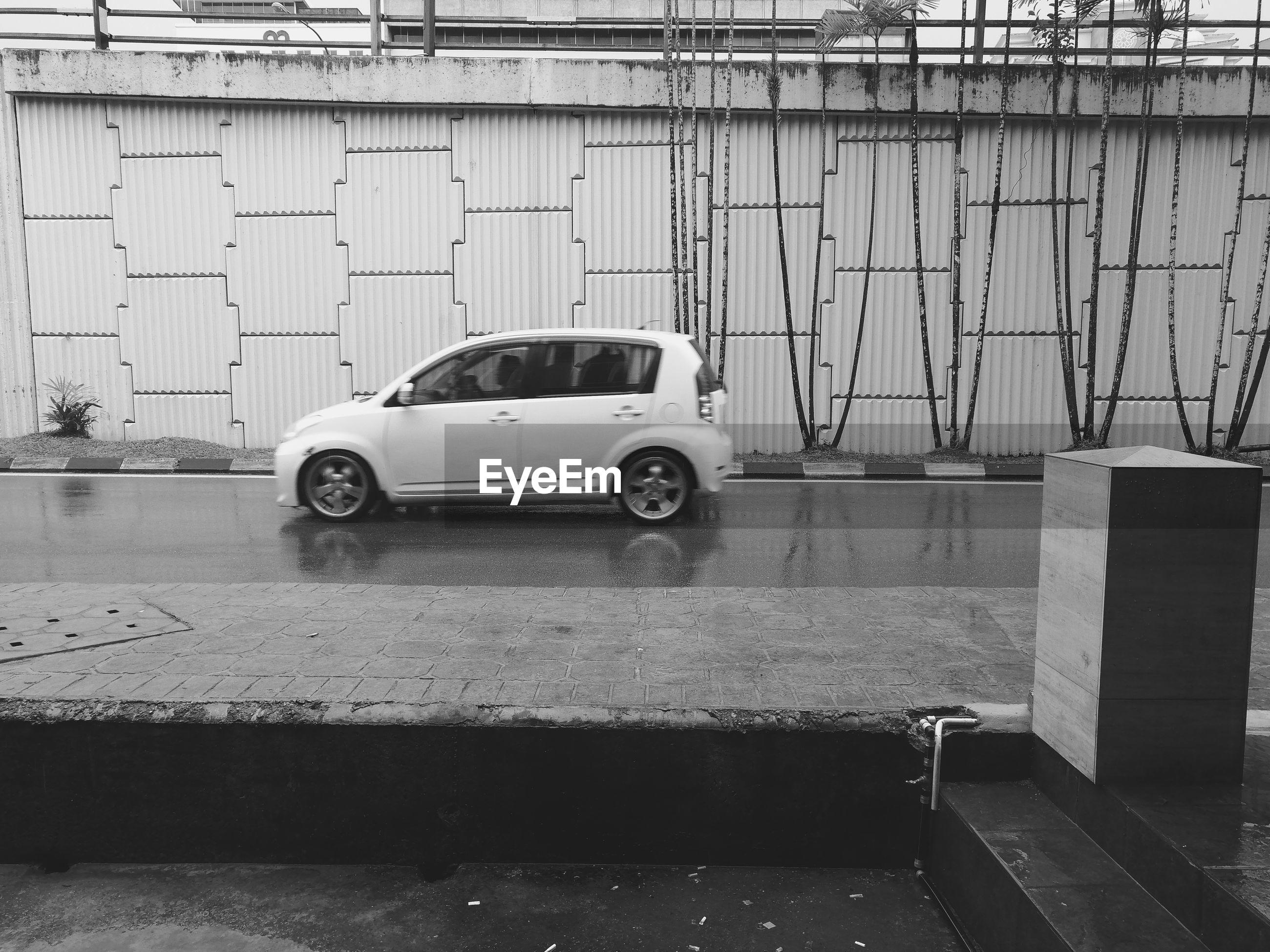 VINTAGE CAR ON ROAD AGAINST BUILDING IN CITY