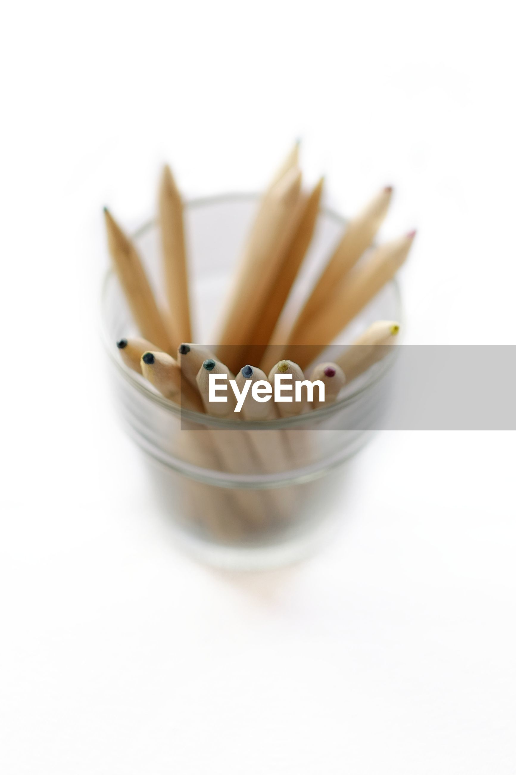 Close up of pencils in jar over white background