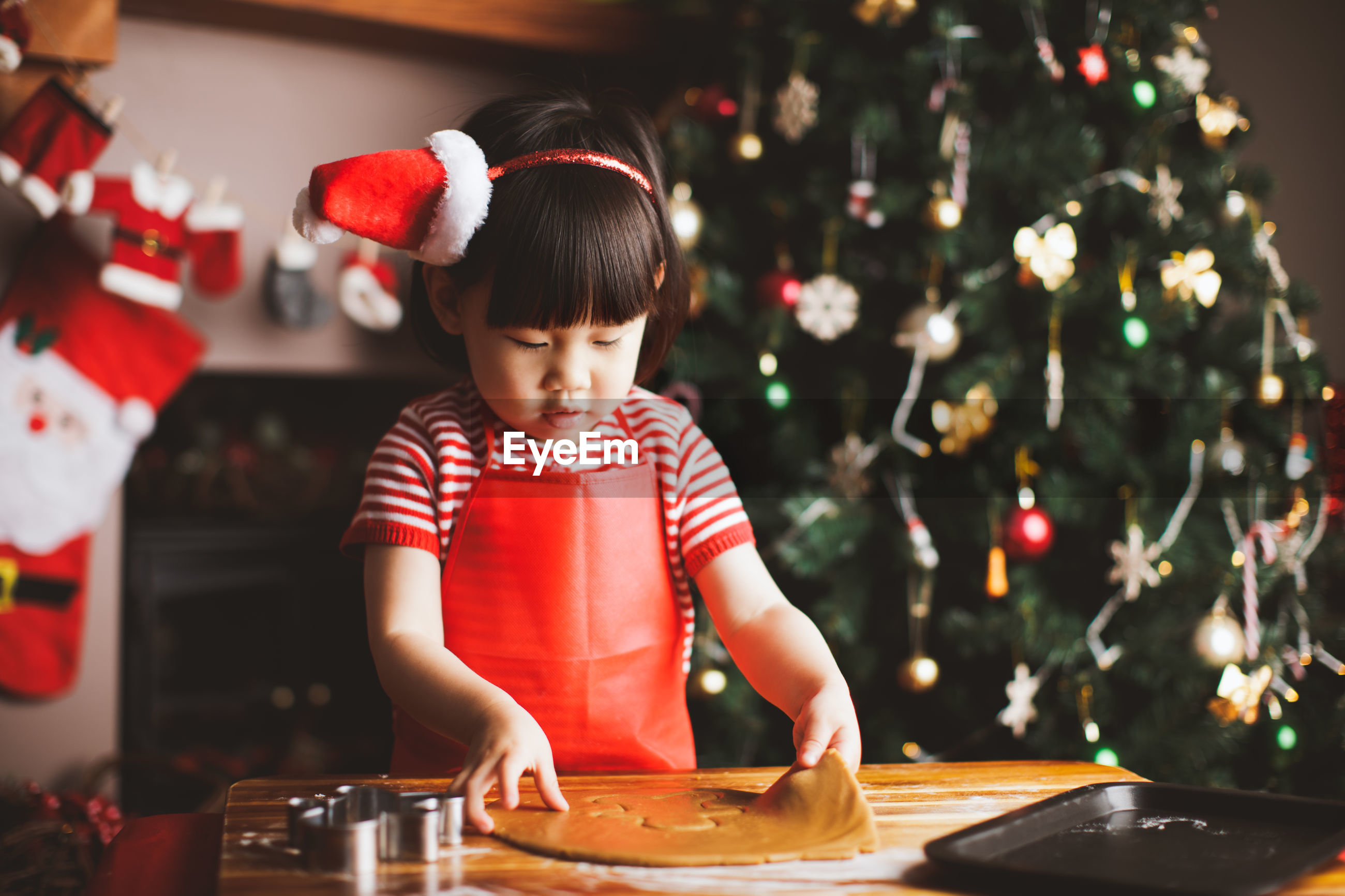 Girl making cookies at table during christmas