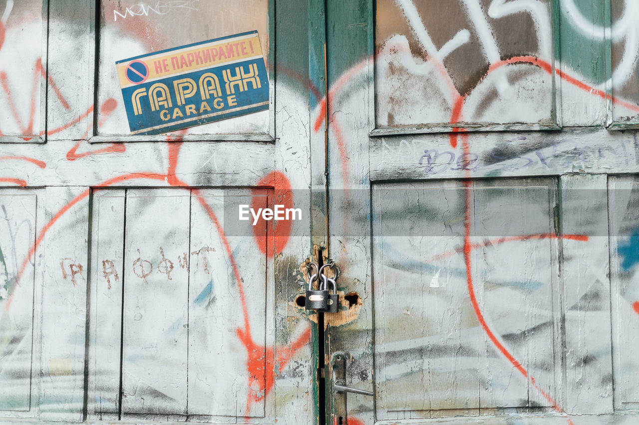 text, western script, communication, day, architecture, no people, sign, graffiti, outdoors, door, built structure, wall - building feature, building exterior, entrance, close-up, guidance, information, closed, capital letter, metal