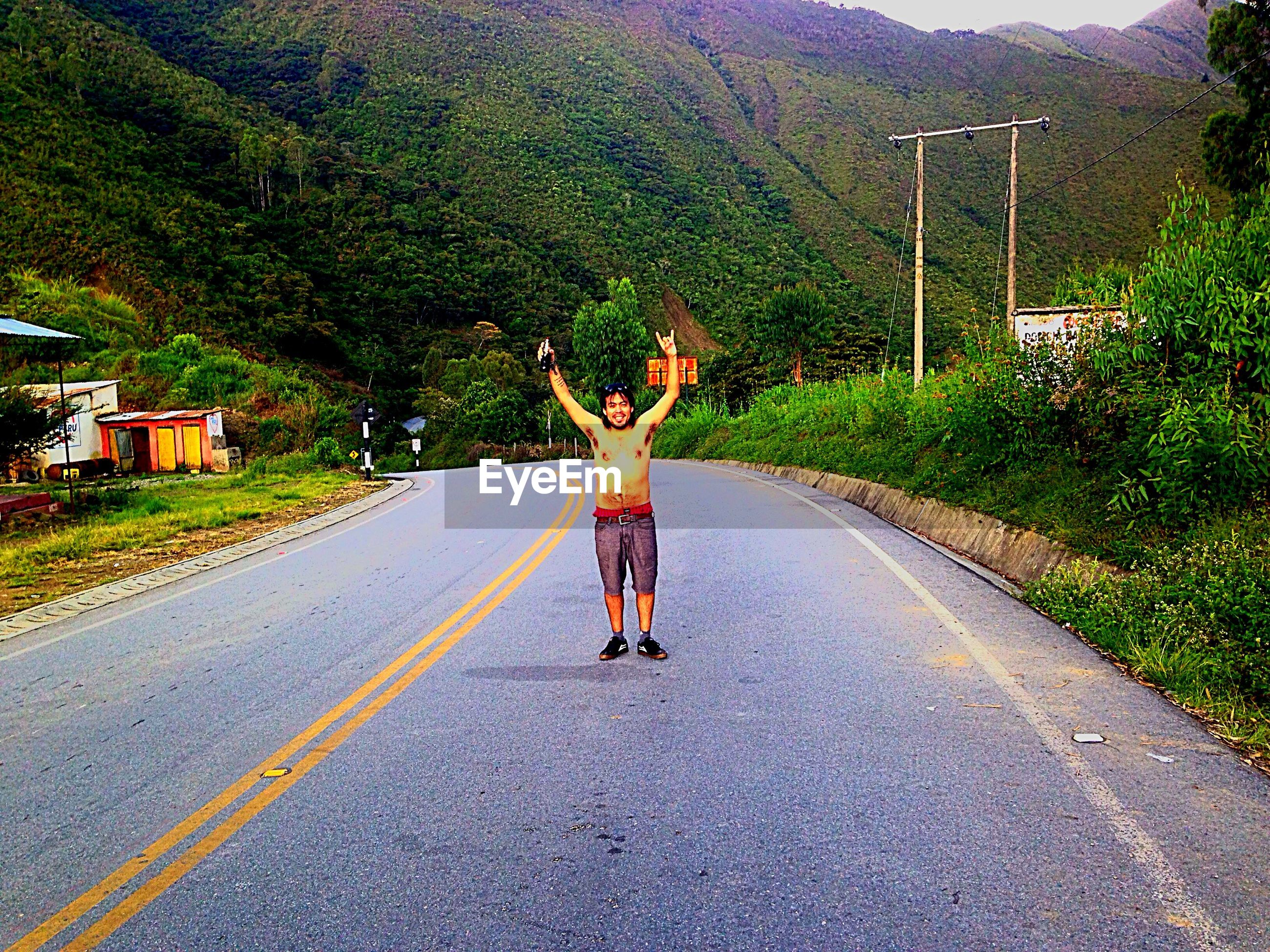 full length, tree, road, lifestyles, leisure activity, the way forward, transportation, casual clothing, walking, street, rear view, country road, day, road marking, outdoors, diminishing perspective, men, mountain