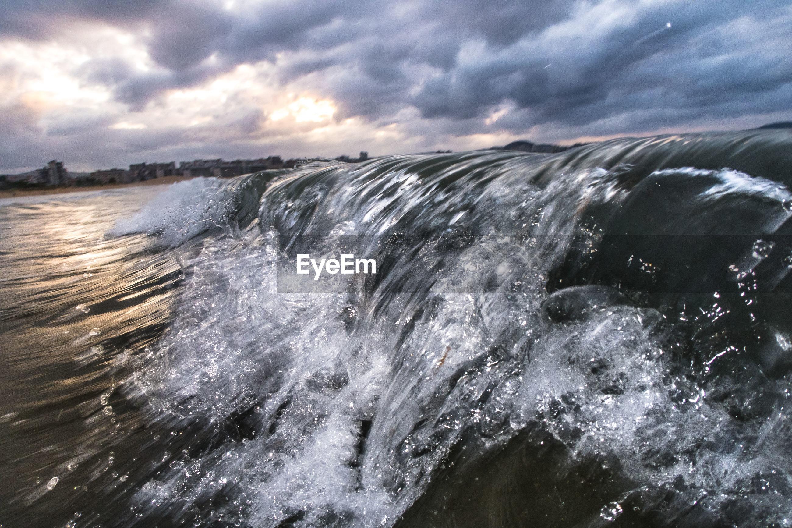 SEA WAVES SPLASHING ON CLOUDY SKY