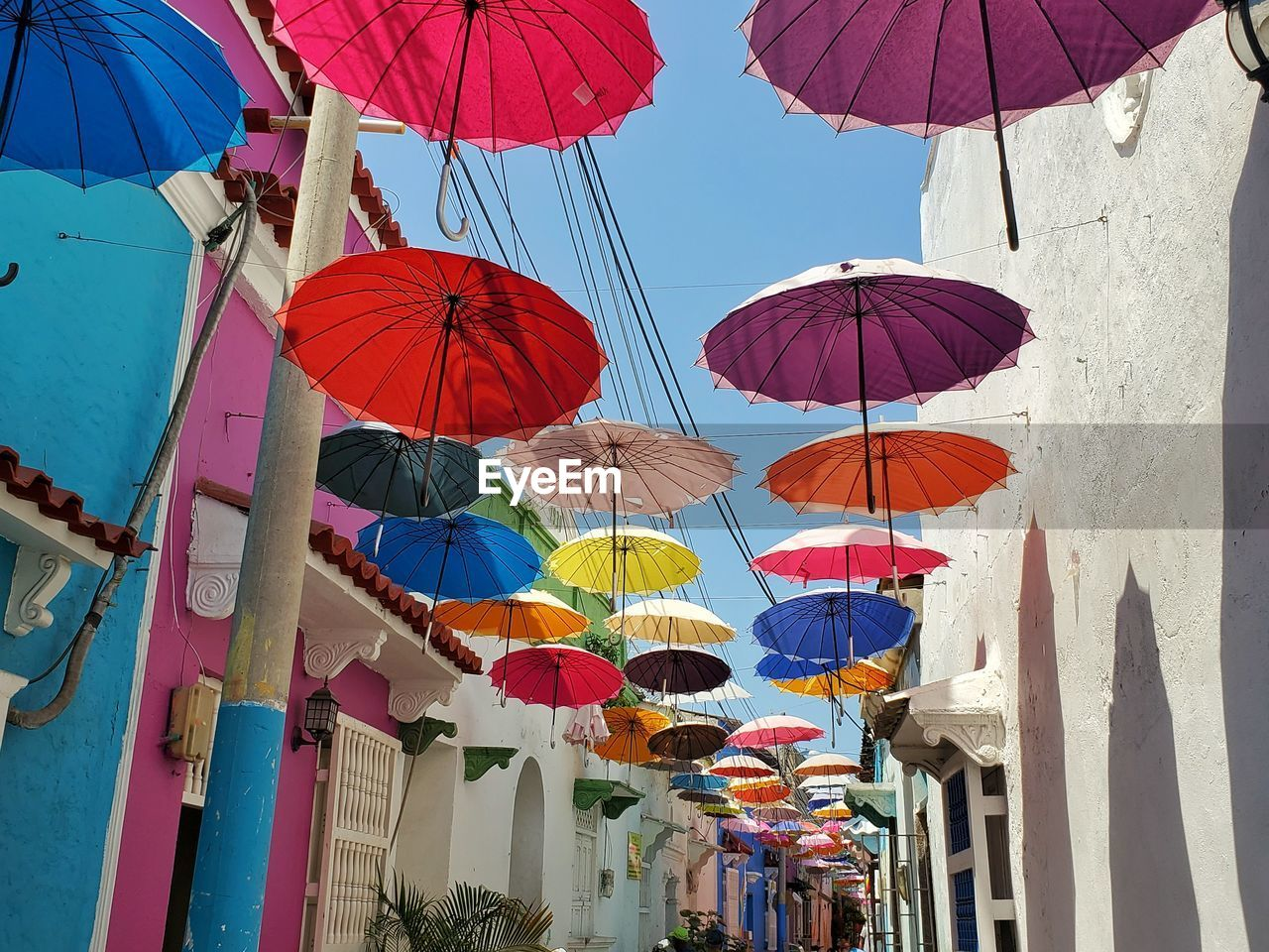 Low angle view of multi colored umbrellas hanging by building against sky in cartagena,  colombia