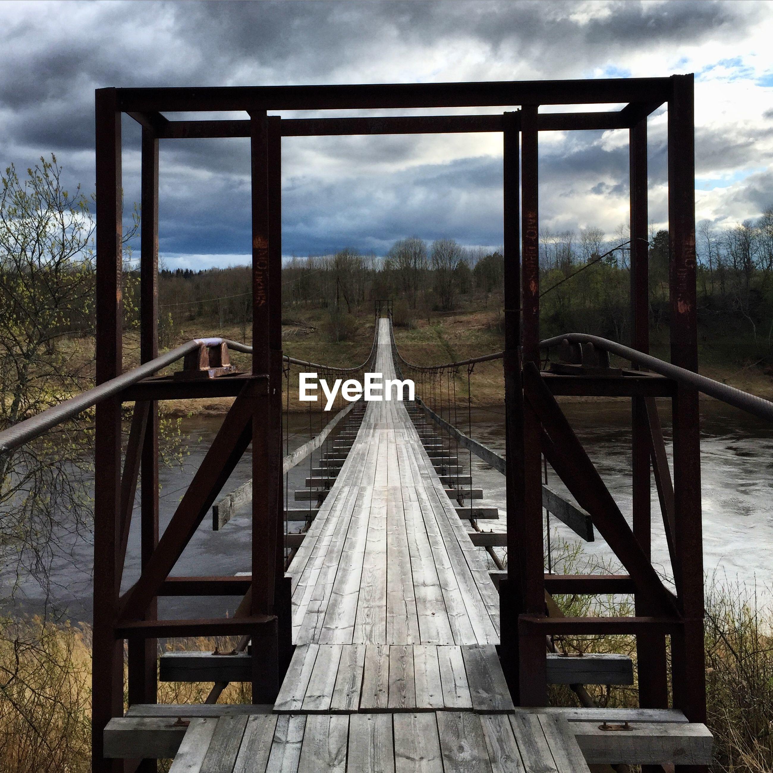 Footbridge over river against cloudy sky