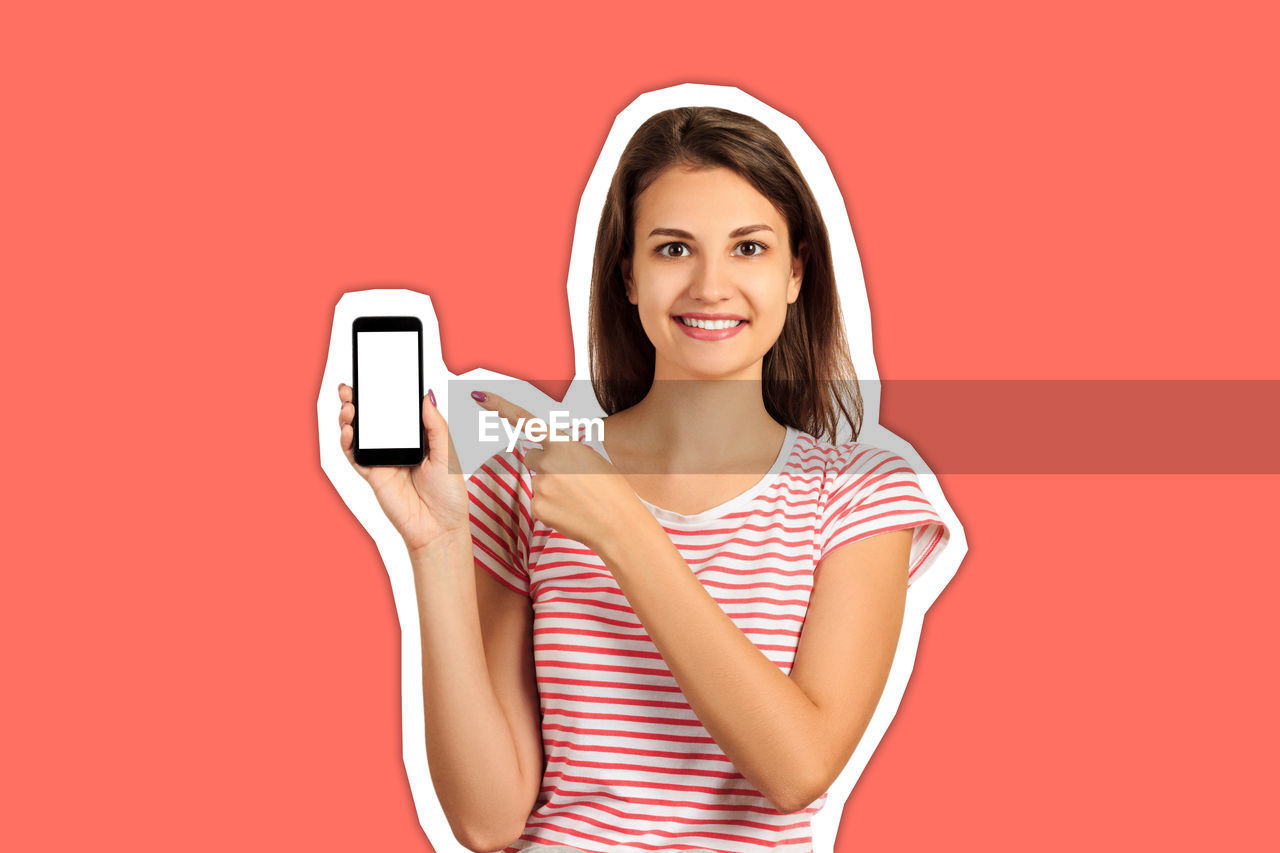 Portrait of young woman pointing at mobile phone cut out against coral background