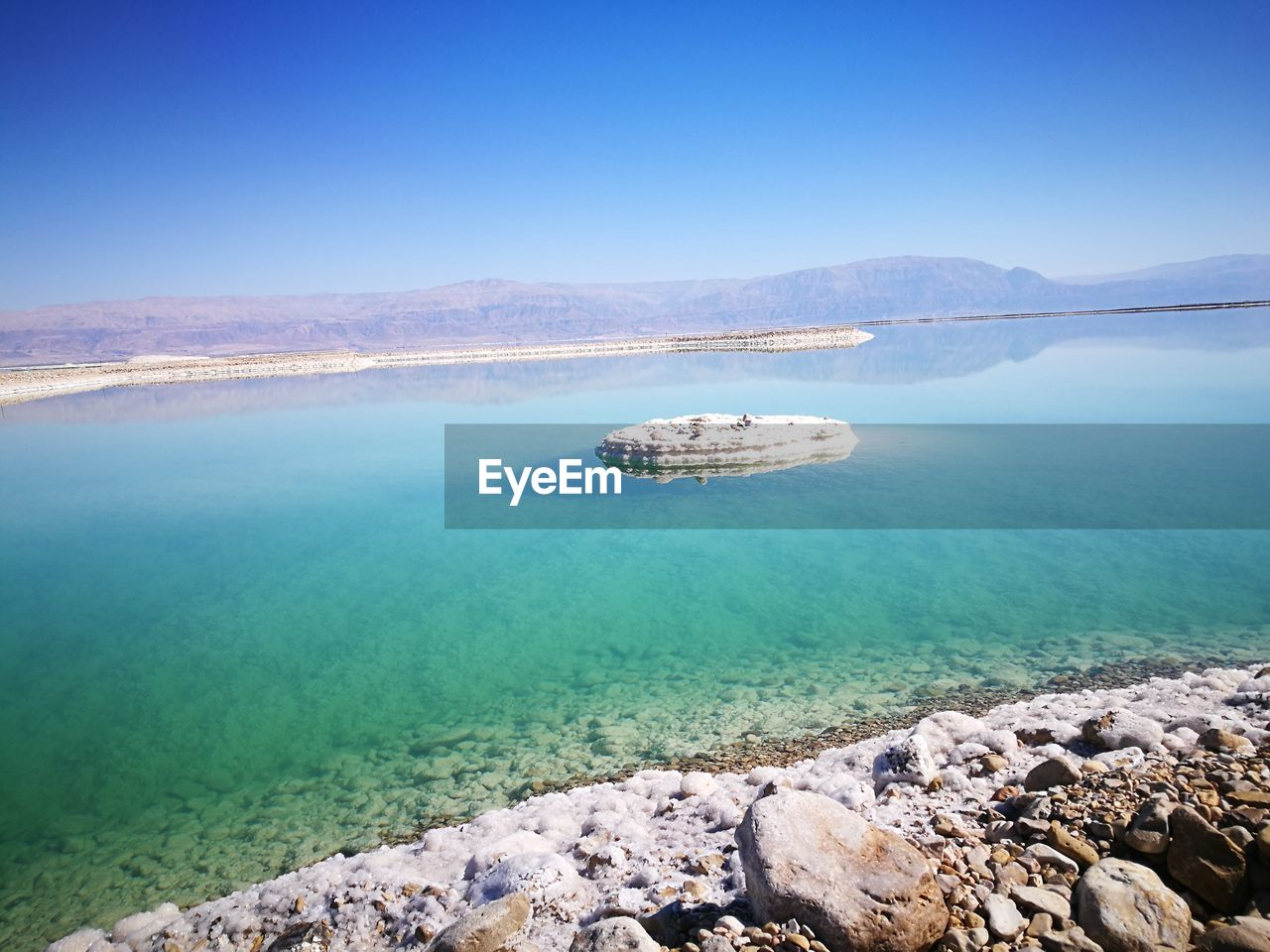 water, beauty in nature, scenics - nature, tranquil scene, sky, blue, tranquility, rock, solid, rock - object, nature, sea, day, clear sky, no people, land, idyllic, non-urban scene, copy space, outdoors, turquoise colored, shallow