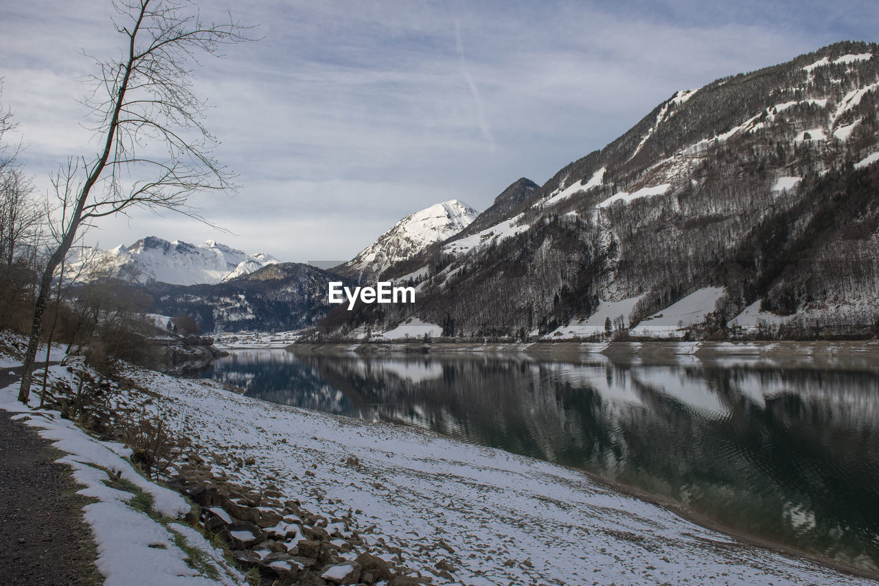 cold temperature, winter, snow, mountain, scenics - nature, beauty in nature, water, sky, tranquil scene, tranquility, nature, lake, snowcapped mountain, cloud - sky, no people, mountain range, tree, non-urban scene, outdoors