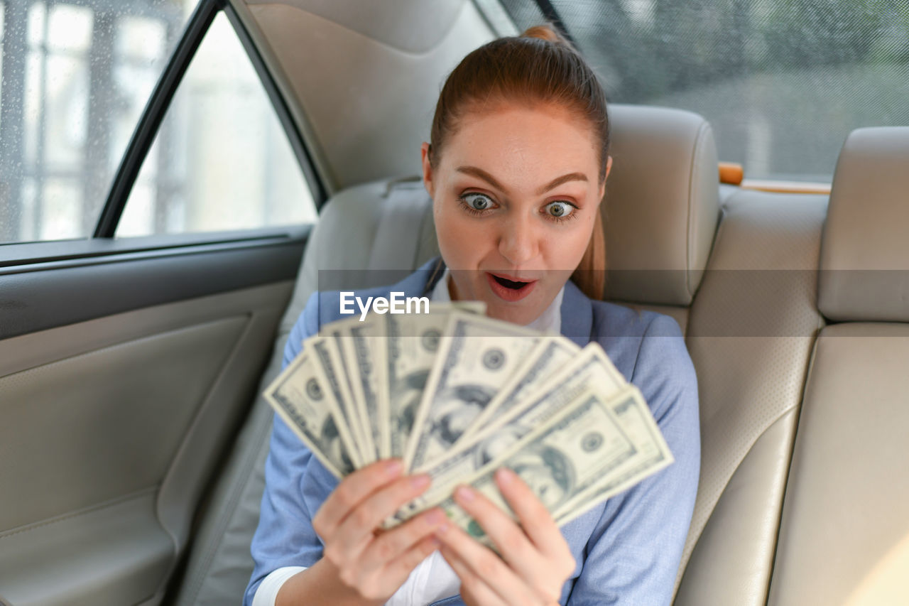 Surprised businesswoman looking at paper currency while sitting in car