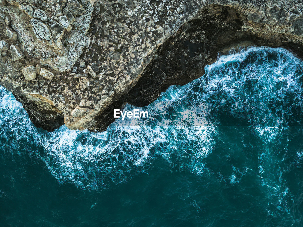 rock, rock - object, solid, sea, water, nature, rock formation, sport, beauty in nature, motion, no people, waterfront, day, outdoors, high angle view, wave, geology, textured, blue, power in nature, turquoise colored