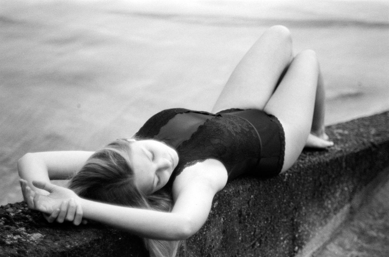 Full length of woman lying on retaining wall