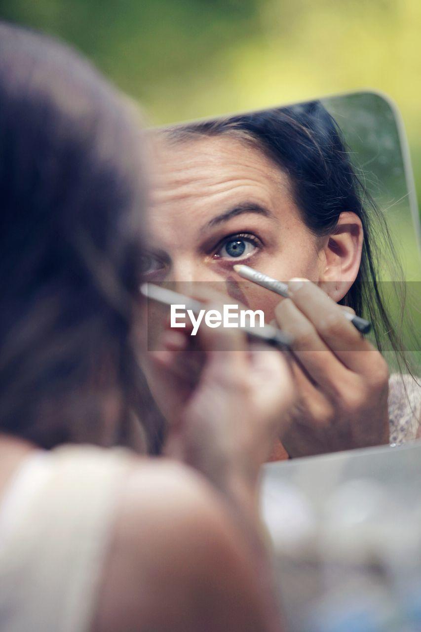 Reflection of woman applying eyeliner on mirror