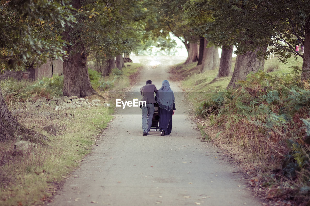 Rear View Of Man And Woman Walking On Road Amidst Trees At Park
