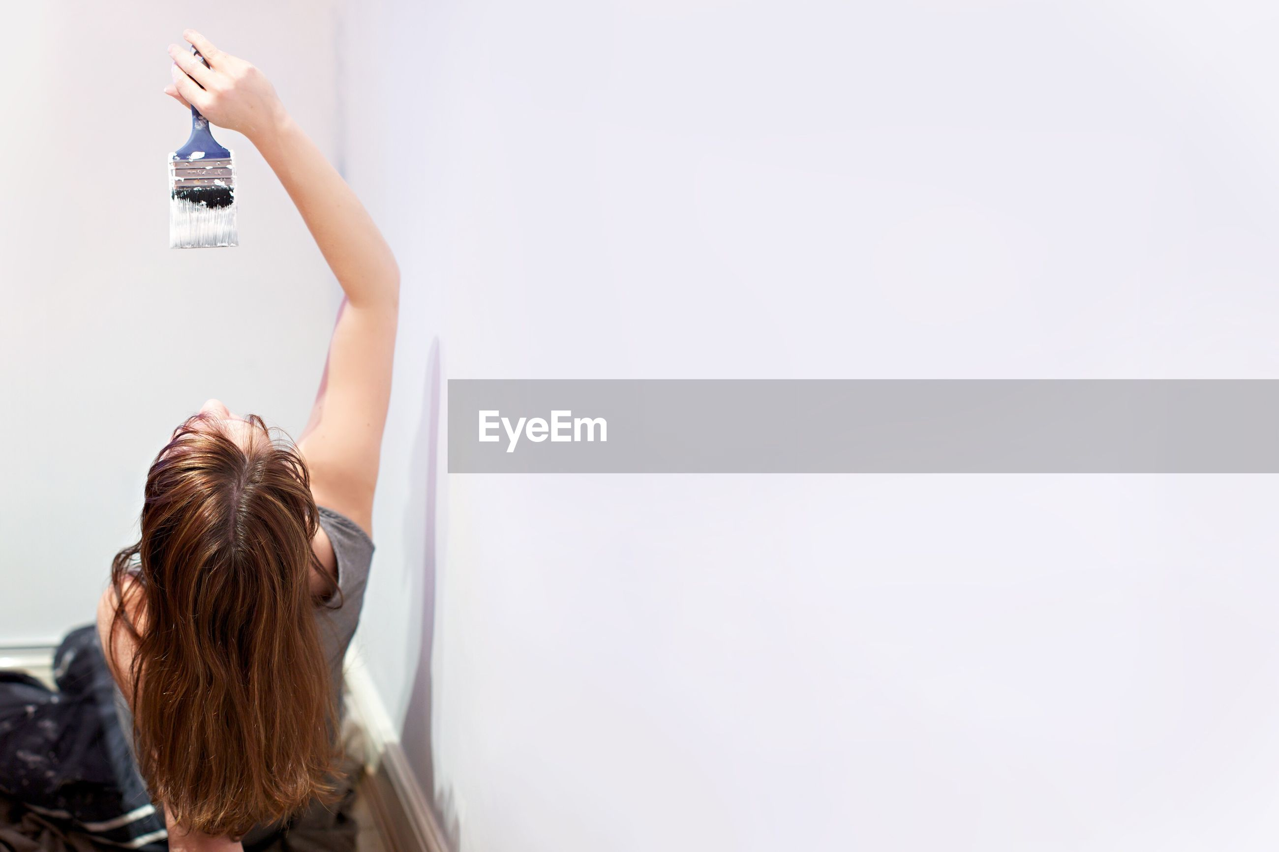 High angle view of woman painting on wall using paintbrush