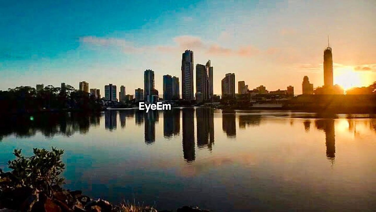 skyscraper, urban skyline, architecture, reflection, city, building exterior, cityscape, built structure, modern, sky, travel destinations, sunset, downtown district, waterfront, no people, water, outdoors, cloud - sky, scenics, tree, day